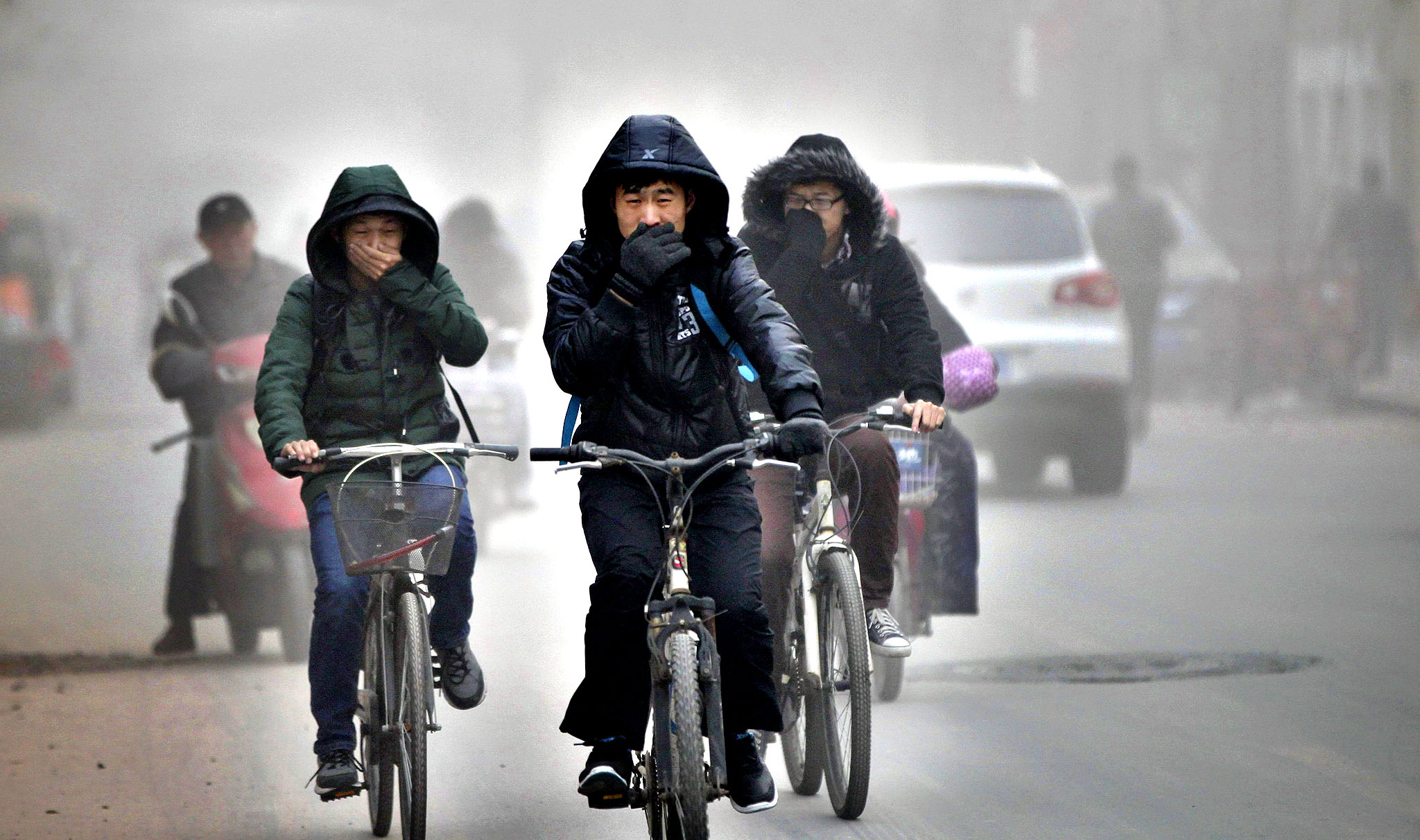 "Residents cover their face from dust as they ride their bicycles along a street on a hazy day in Zhengzhou, Henan province. Commentaries by two of China's most influential news outlets suggesting that an ongoing air pollution crisis was not without a silver lining drew a withering reaction on Tuesday from internet users and other media. The Global Times said smog could be useful in military situations, as it could hinder the use of guided missiles, while CCTV listed five ""unforeseen rewards"" for smog, including helping Chinese people's sense of humour."