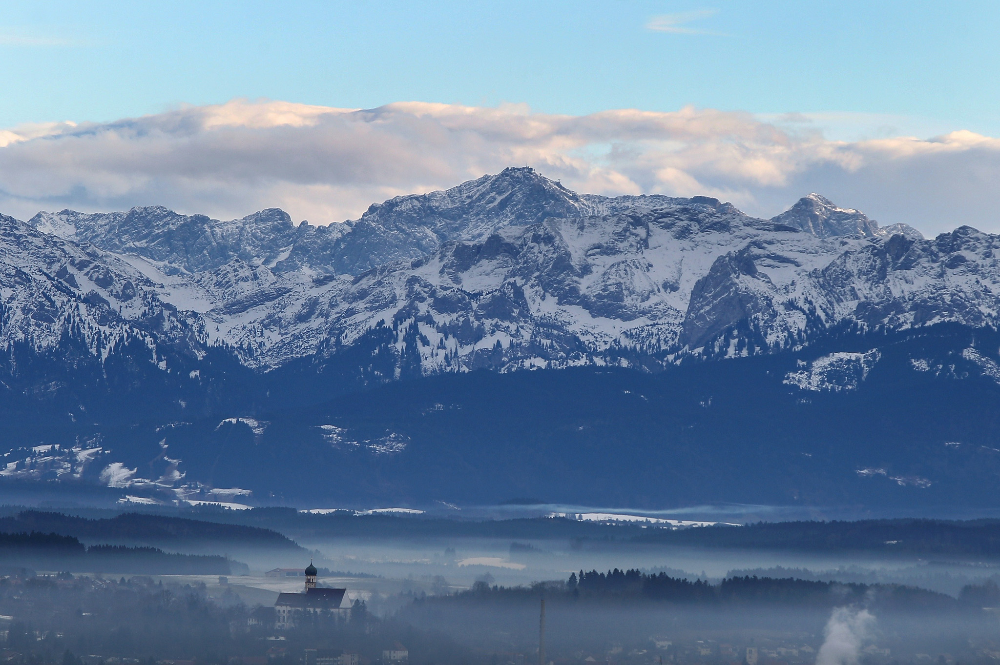 Fog rises from the valley and the church...Fog rises from the valley and the church of Marktoberdorf, southern Germany, as in background can be seen an Alps panorama on January 19, 2014.       AFP PHOTO / DPA / KARL-JOSEF HILDENBRAND / GERMANY OUTKARL-JOSEF HILDENBRAND/AFP/Getty Images