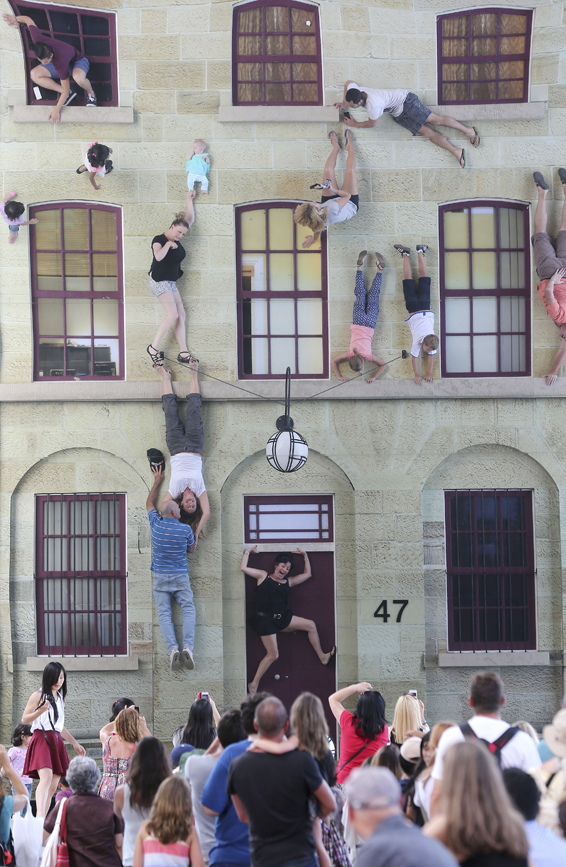 "Onlookers watch as people pretend to hang off ledges and windowsills on an unusual architectural display, called ""Merchants Store,"" during the Sydney Festival in Sydney Monday, Jan. 13, 2014. Merchant Store is a mirror illusion art piece designed to give the impression of hanging off the outside of a building up high while really being safe on the ground. The festival is an arts-based event held in January each year boasting local and international artists in contemporary and classical music, dance, circus, drama and visual arts. (AP Photo/Rob Griffith)"