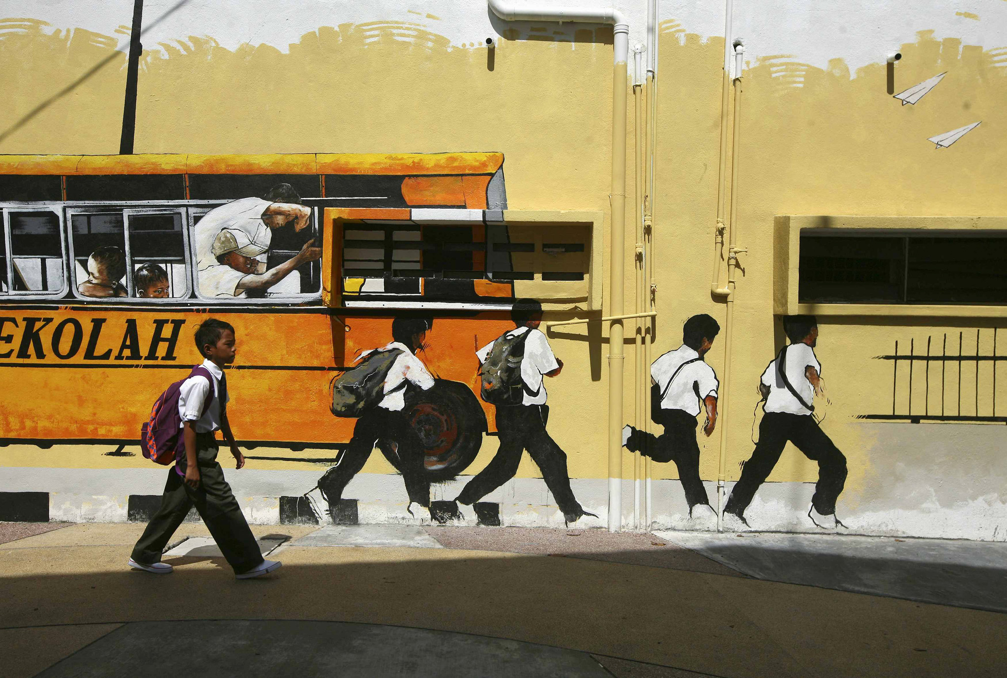 A school boy walks past a street mural depicting a school bus and students in Shah Alam, outside Kuala Lumpur...A school boy walks past a street mural depicting a school bus and students in Shah Alam, outside Kuala Lumpur January 2, 2014. Malaysia begins the first day of the new school year of 2014 on January 2. REUTERS/Samsul Said