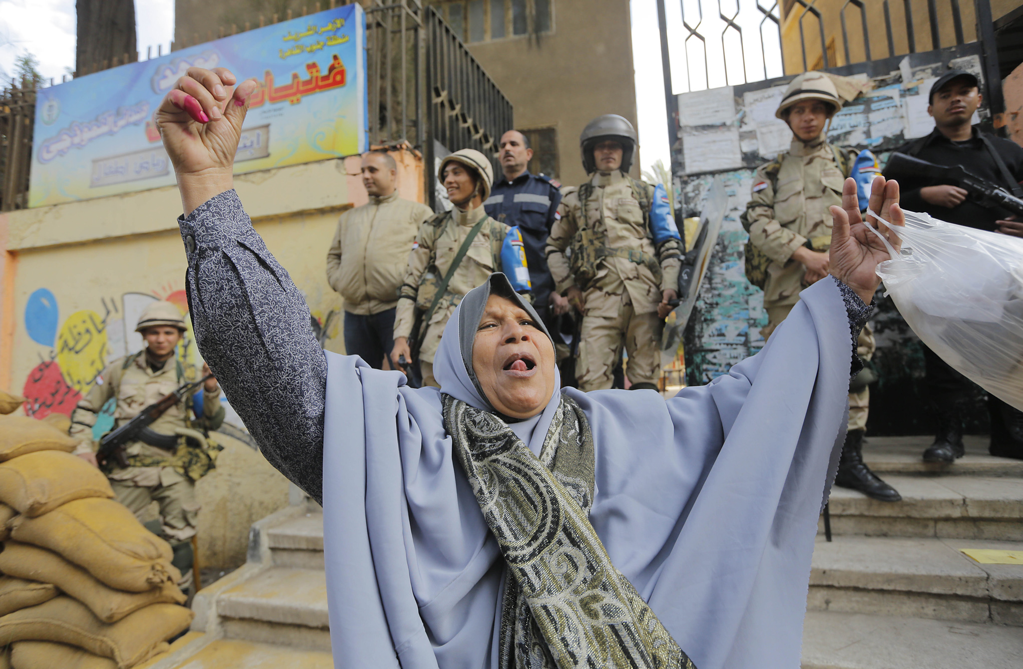 An Egyptian ululates in front of a polling station after casting her vote in Cairo, Egypt, Tuesday, Jan. 14, 2014. Egyptians have started voting on a draft for their country's new constitution that represents a key milestone in a military-backed roadmap put in place after President Mohammed Morsi was overthrown in a popularly backed coup last July. (AP Photo/Amr Nabil)