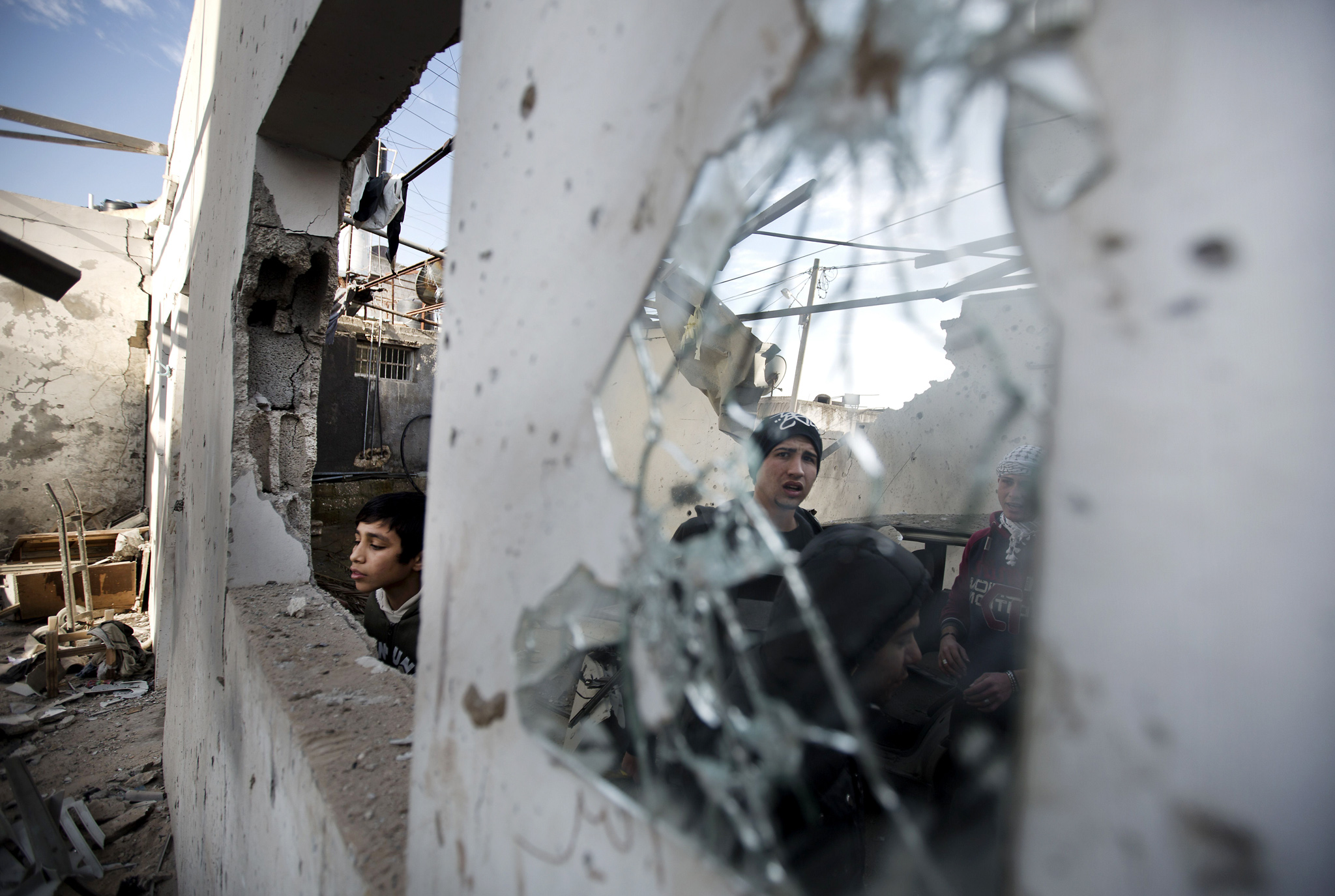 Palestinian youths check a destroyed building following overnight Israeli air strikes in Gaza City on January 16, 2014. Israeli air strikes in the Gaza Strip against training camps used by the armed wing of the territory's Hamas rulers left four children and a woman wounded, Palestinian medical sources said.