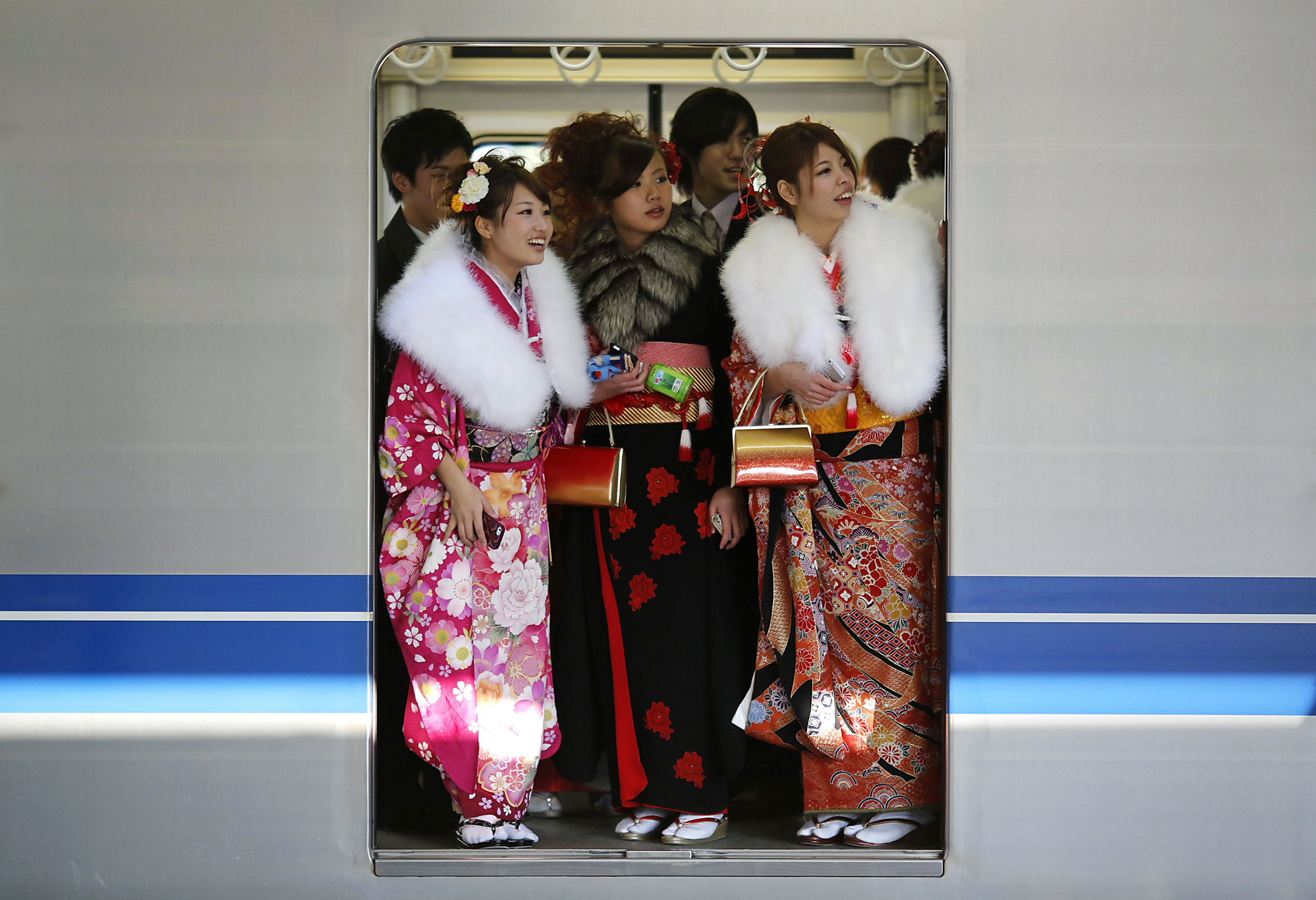 Japanese women in kimonos ride a train after a ceremony celebrating Coming of Age Day at an amusement park in Tokyo...Japanese women in kimonos ride a train after a ceremony celebrating Coming of Age Day at an amusement park in Tokyo January 13, 2014. According to a government announcement, about 1,210,000 men and women who were born in 1993 reached coming of age this year and the number is 10,000 less people than last year. The figure is the smallest number since the government started counting in 1968. REUTERS/Yuya Shino