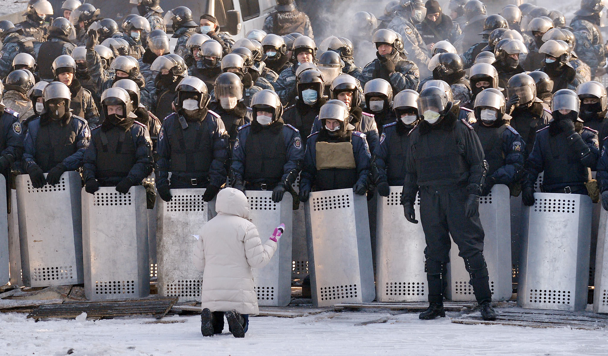 A woman speaks as she kneels down in fro...A woman speaks as she kneels down in front of a line of riot police in the center of Kiev on January 24, 2014. Ukrainian protesters today expanded their protest camp in Kiev closer to the administration of President Viktor Yanukovych, after crisis talks to end Ukraine's worst crisis since its 1991 independence ended in deadlock. After five days of clashes that activists say left five dead, Ukraine's three main opposition leaders held several hours of talks with Yanukovych late on January 23 but the minor concessions they announced were greeted with derision by protesters. AFP PHOTO / SERGEI SUPINSKYSERGEI SUPINSKY/AFP/Getty Images