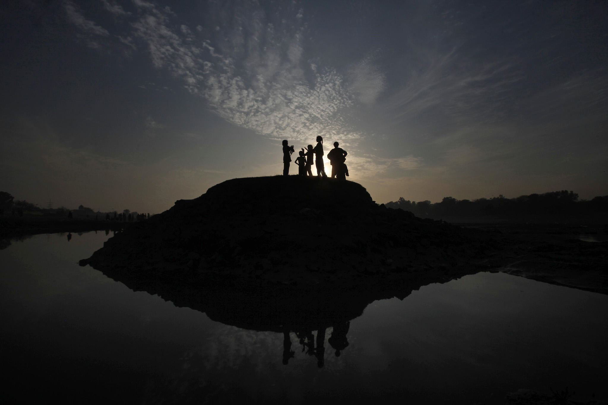 Children are silhouetted against the setting sun as they play on the outskirts of Lahore January 28, 2014.