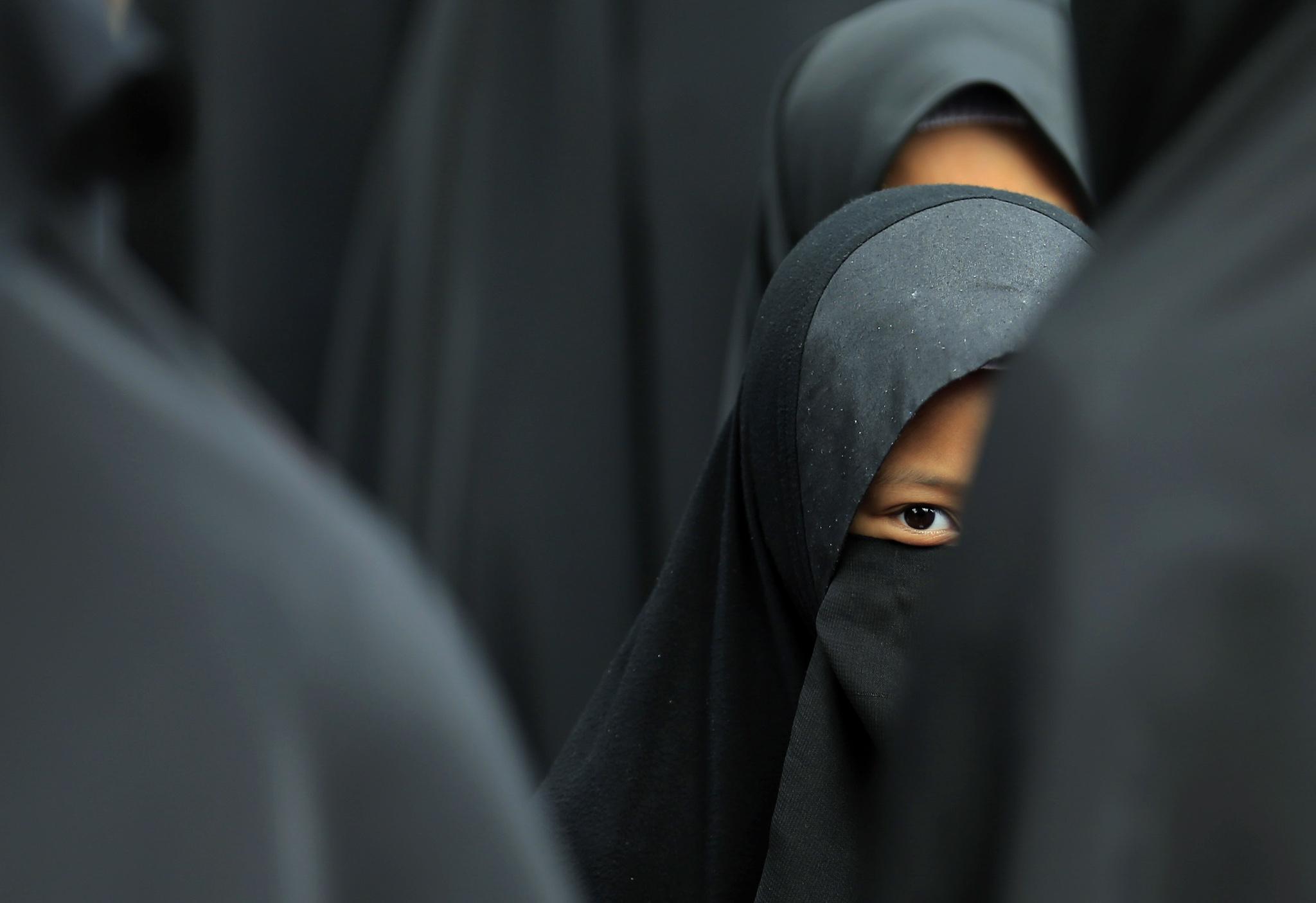 A girl wearing a hijab waits at the Shah Alam stadium during celebrations of Maulidur Rasul, or the birth of Prophet Muhammad, outside Kuala Lumpur...A girl wearing a hijab waits at the Shah Alam stadium during celebrations of Maulidur Rasul, or the birth of Prophet Muhammad, outside Kuala Lumpur