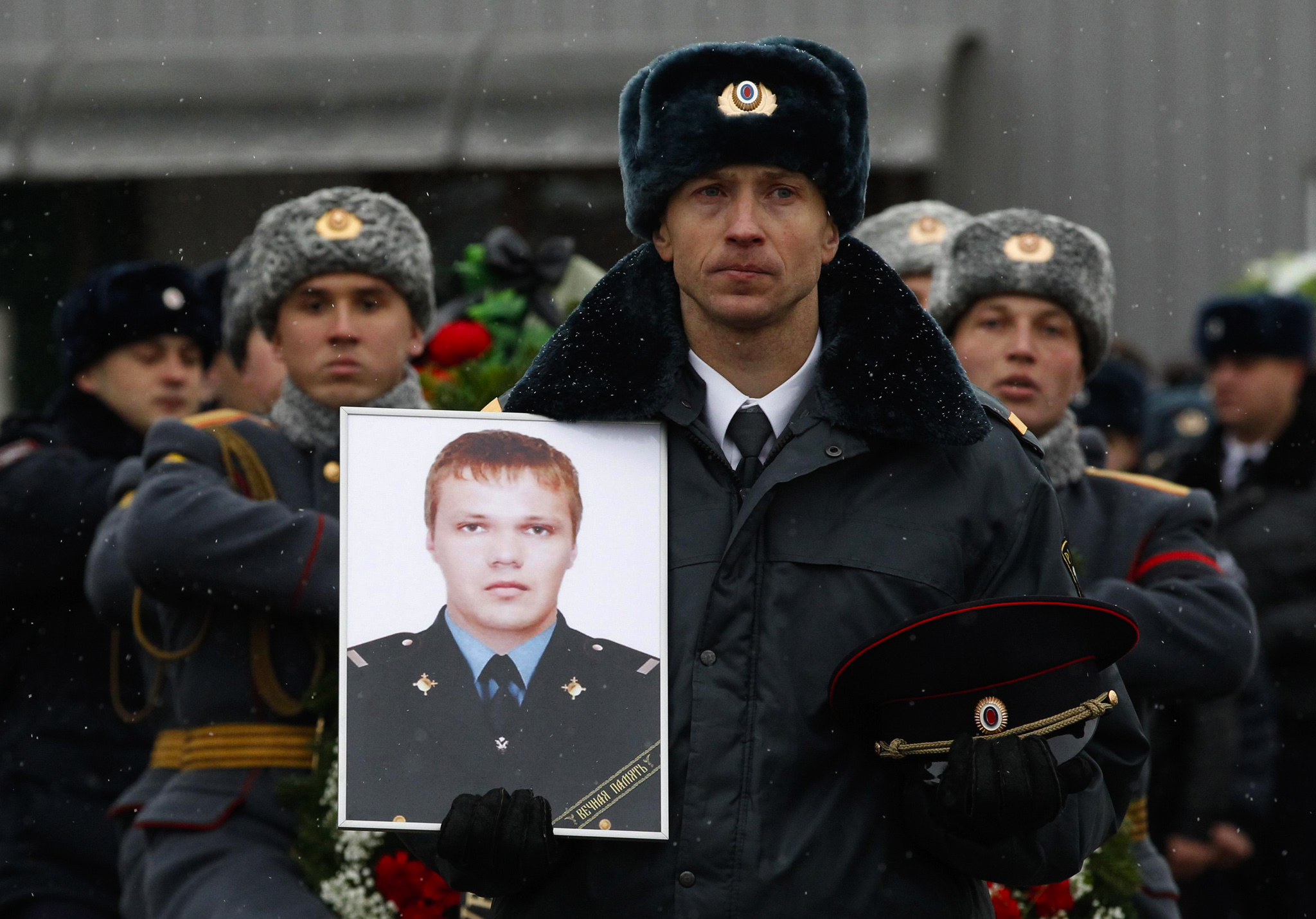 A police officer carries a portrait of Russian police senior sergeant Dmitry Makovkin, who was killed by a suicide bomb blast in Volgograd's main railway station, in front of the funeral procession carrying Makovkin's coffin.