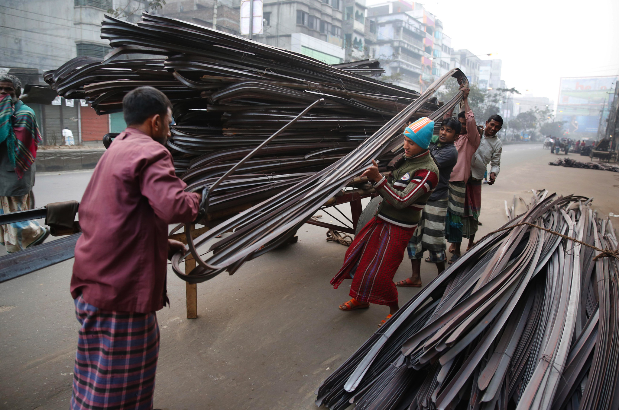 Workers unload angle irons used in building construction in Dhaka, Bangladesh.