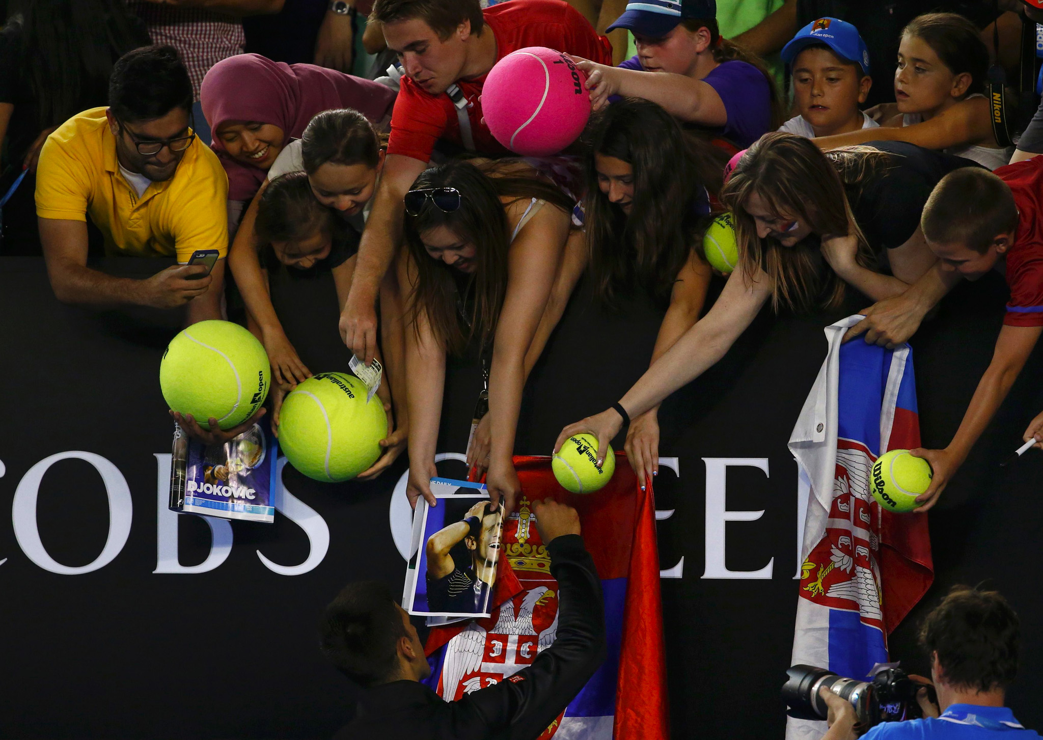Novak Djokovic of Serbia signs autographs after his men's singles match against Lukas Lacko of Slovakia at the Australian Open 2014 tennis tournament in Melbourne