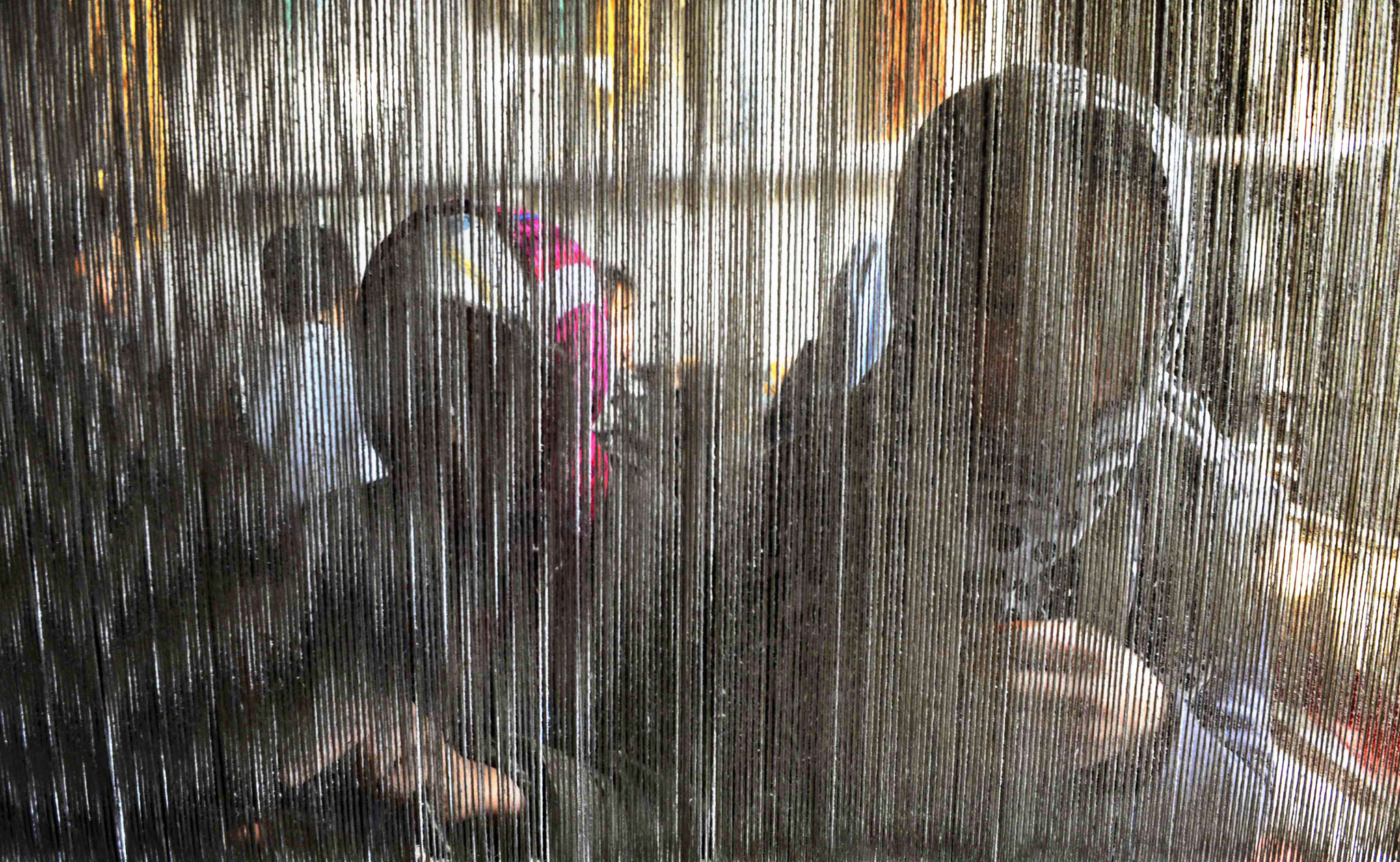 Afghan children weave a carpet at a traditional carpet factory in Herat.