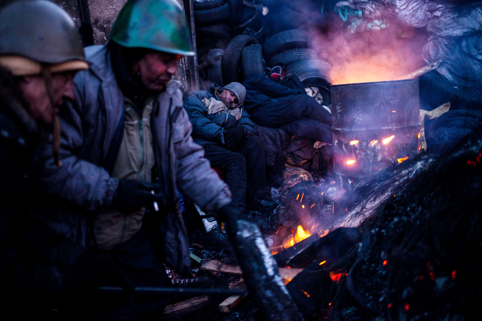 TOPSHOTS Anti-government protesters warm themselves at a fire  near a barricade early morning in Kiev on January 31, 2014. A bill passed by Ukraine's parliament to amnesty arrested activists gives protesters a 15-day deadline to leave occupied streets and administrative buildings otherwise it will not be implemented, according to the text published the day before.