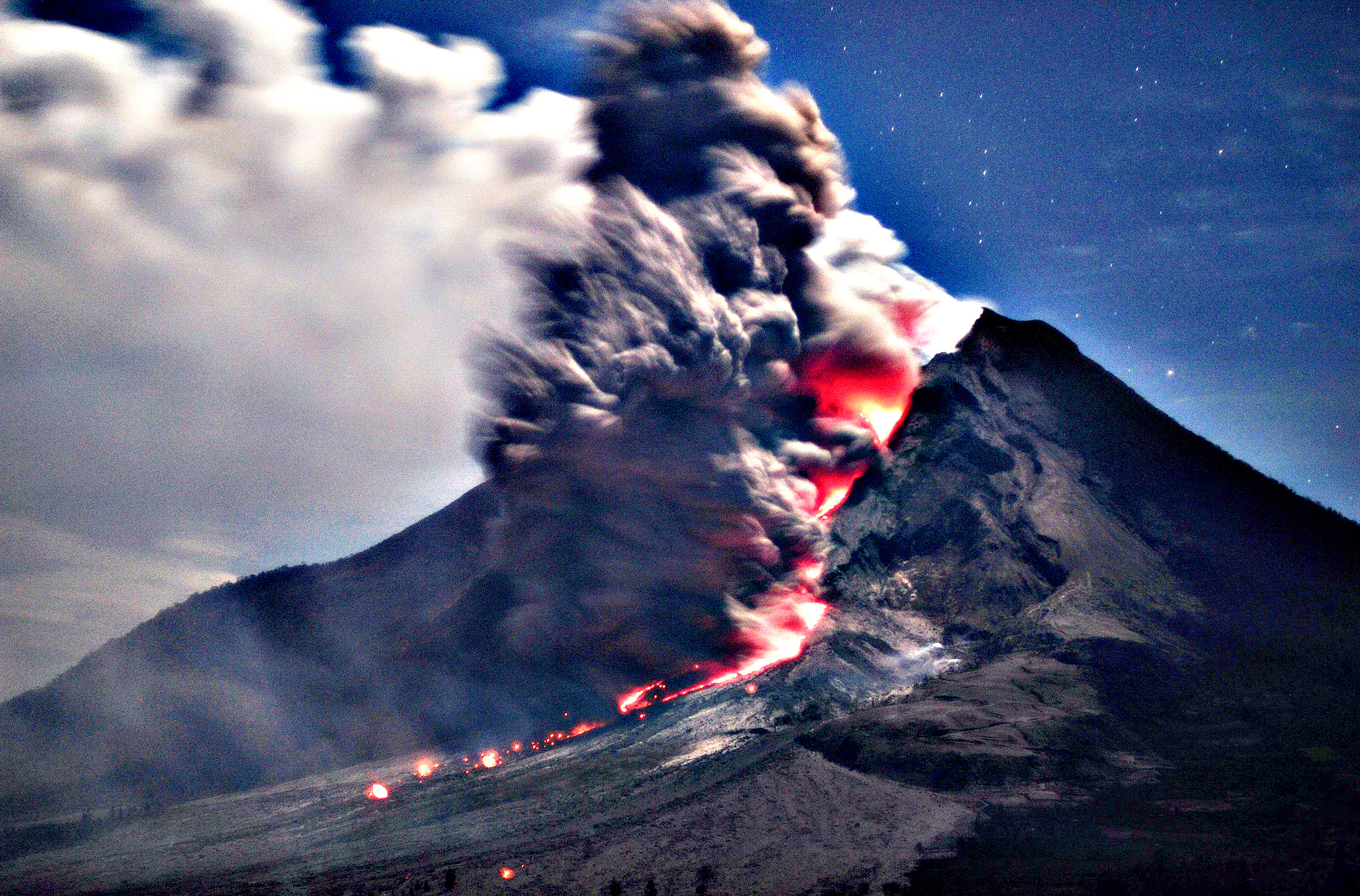 Indonesian men watch Mount Sinabung spewing volcanic materials during an eruption in Tiga Kicat, North Sumatra, Indonesia, Friday, Jan. 3, 2014. The 2,600-meter (8,530-foot) volcano has sporadically erupted since September.