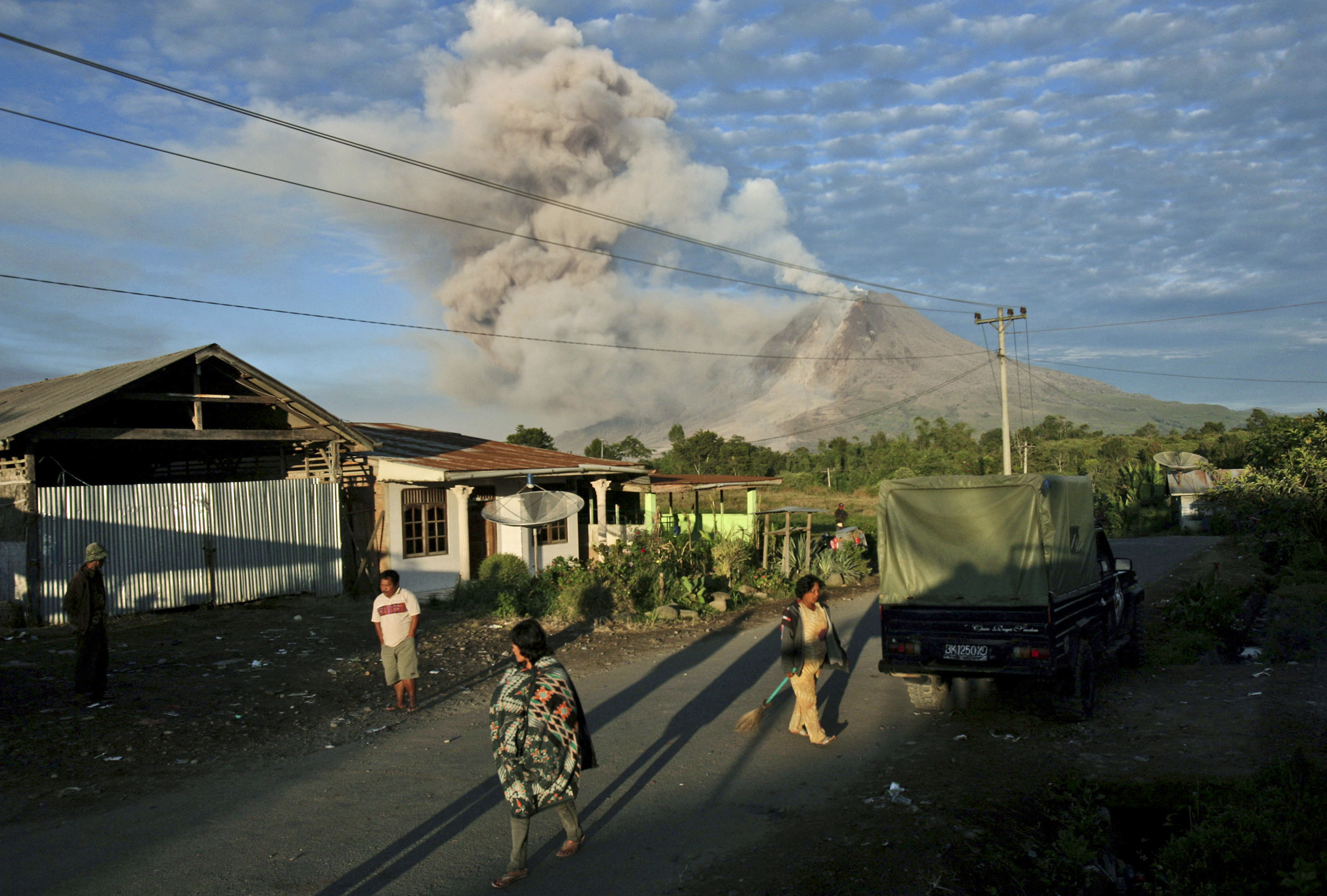 Villagers start their morning routine as Mount Sinabung releases volcanic materials into the air in Perteguhan, North Sumatra, Indonesia, Monday, Jan. 6, 2014. The 2,600-meter (8,530-foot) volcano has sporadically erupted since September. Authorities extended a danger zone around a rumbling volcano in western Indonesia on Sunday after it spewed blistering gas farther than expected, sending panicked residents streaming down the sides of the mountain.