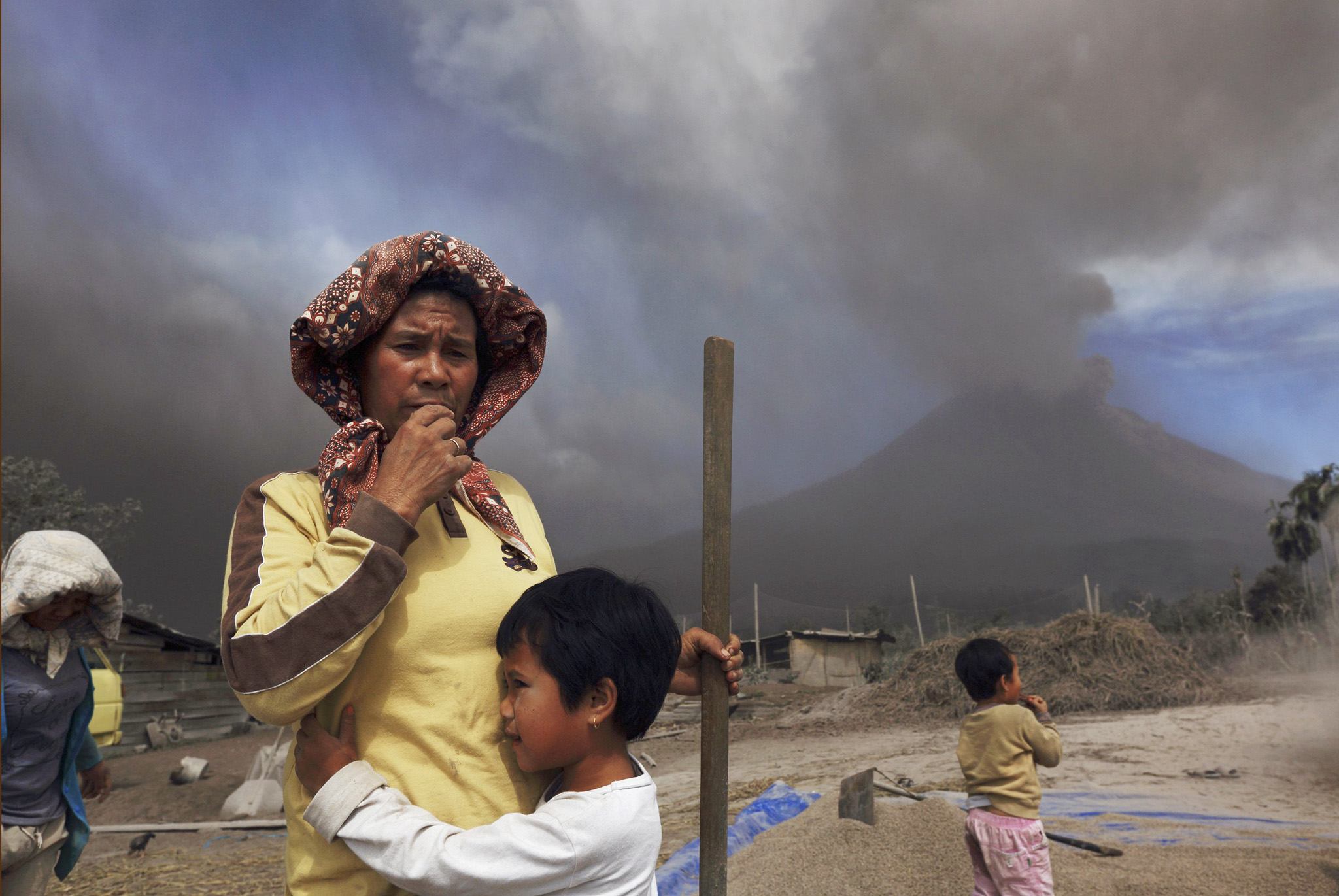 "A child holds her mother next to piles of paddy seeds as ash and smoke fill the air during an eruption in Mount Sinabung at Tiga Pancur village in Karo district, Indonesia's North Sumatra province.   REUTERS/Beawiharta    REUTERS NEWS PICTURES HAS NOW MADE IT EASIER TO FIND THE BEST PHOTOS FROM THE MOST IMPORTANT STORIES AND TOP STANDALONES EACH DAY. Search for ""TPX"" in the IPTC Supplemental Category field or ""IMAGES OF THE DAY"" in the Caption field and you will find a selection of 80-100 of our daily Top Pictures."