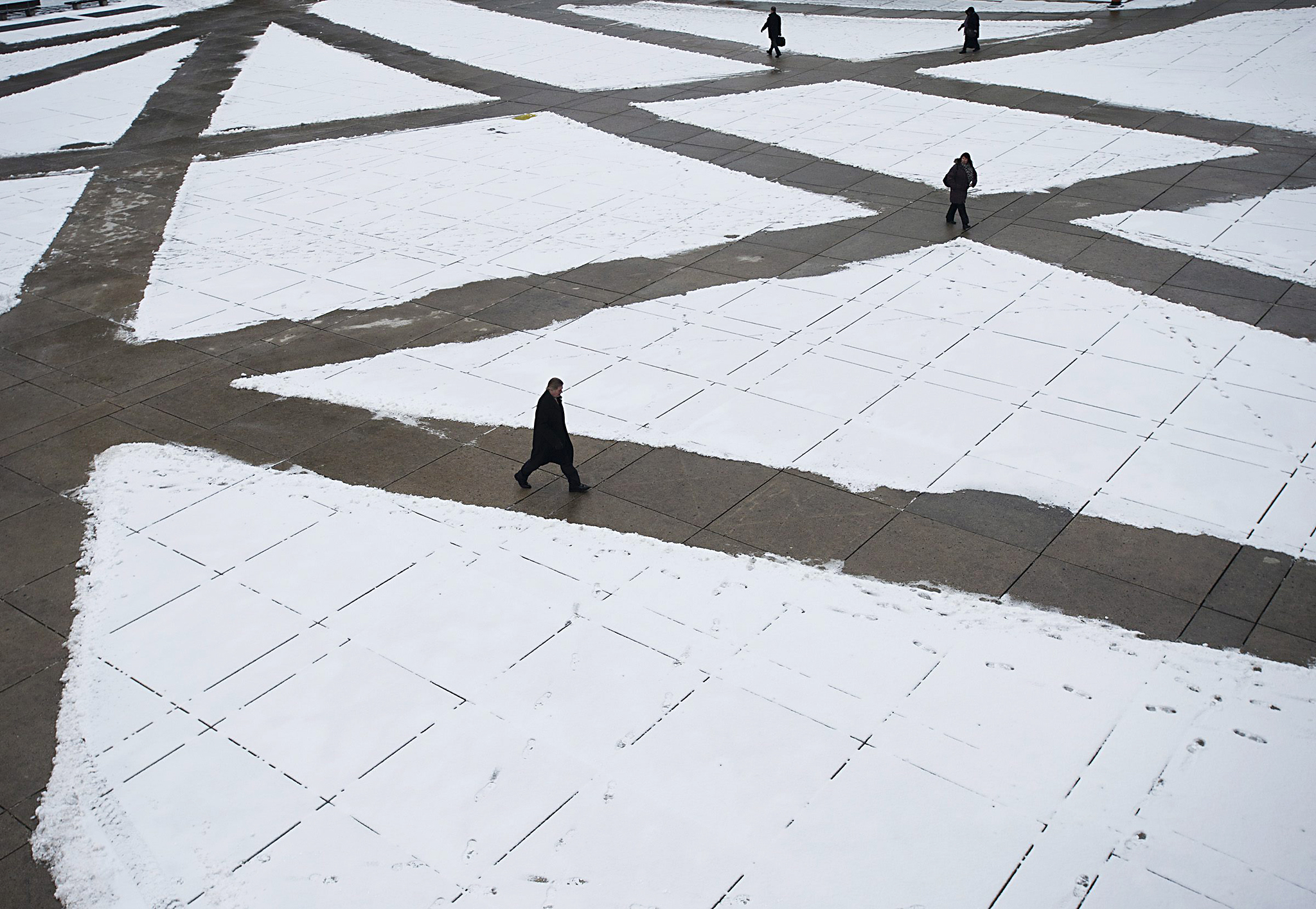 People make their way on plowed paths in the frigid temperatures outside city hall in Toronto on Monday, Jan. 20, 2014.