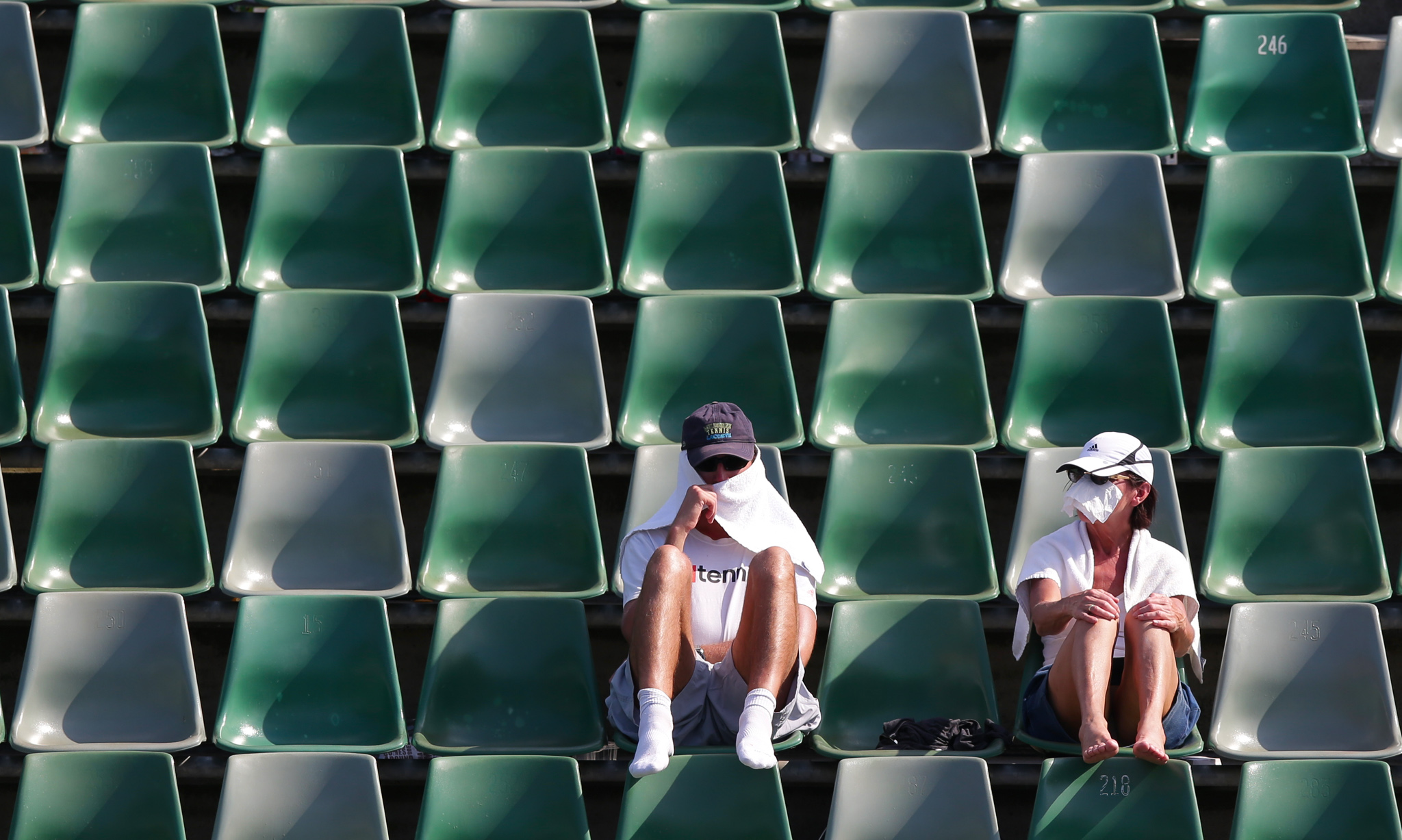 Tennis fans protect themselves from the sun during a first round match at the Australian Open tennis championship in Melbourne, Australia, Tuesday, Jan. 14, 2014.