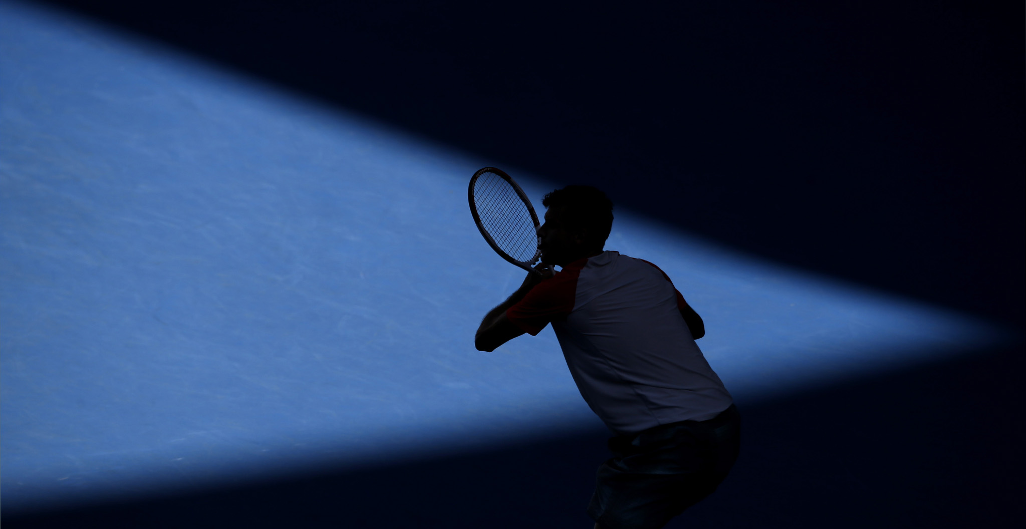 Grigor Dimitrov of Bulgaria is silhouetted as he plays Rafael Nadal of Spain during their quarterfinal at the Australian Open tennis championship in Melbourne, Australia, Wednesday, Jan. 22, 2014.