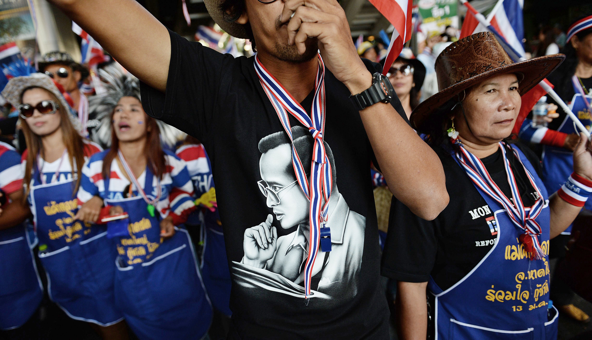 "A Thai anti-government protester wearing...A Thai anti-government protester wearing a T-shirt carrying a picture of King Bhumibol Adulyadej, blows a whistles as he takes part in a march through downtown Bangkok on January 15, 2014.  Two people were wounded in a shooting at an opposition rally in the Thai capital on January 15, authorities said, as protest leaders marched through plush city neighbourhoods in their bid to oust the premier. The demonstrators, backed by the kingdom's royalist establishment, want Prime Minister Yingluck Shinawatra to resign to make way for an unelected ""people's council"" that would oversee reforms to curb the political dominance of her billionaire brother Thaksin."