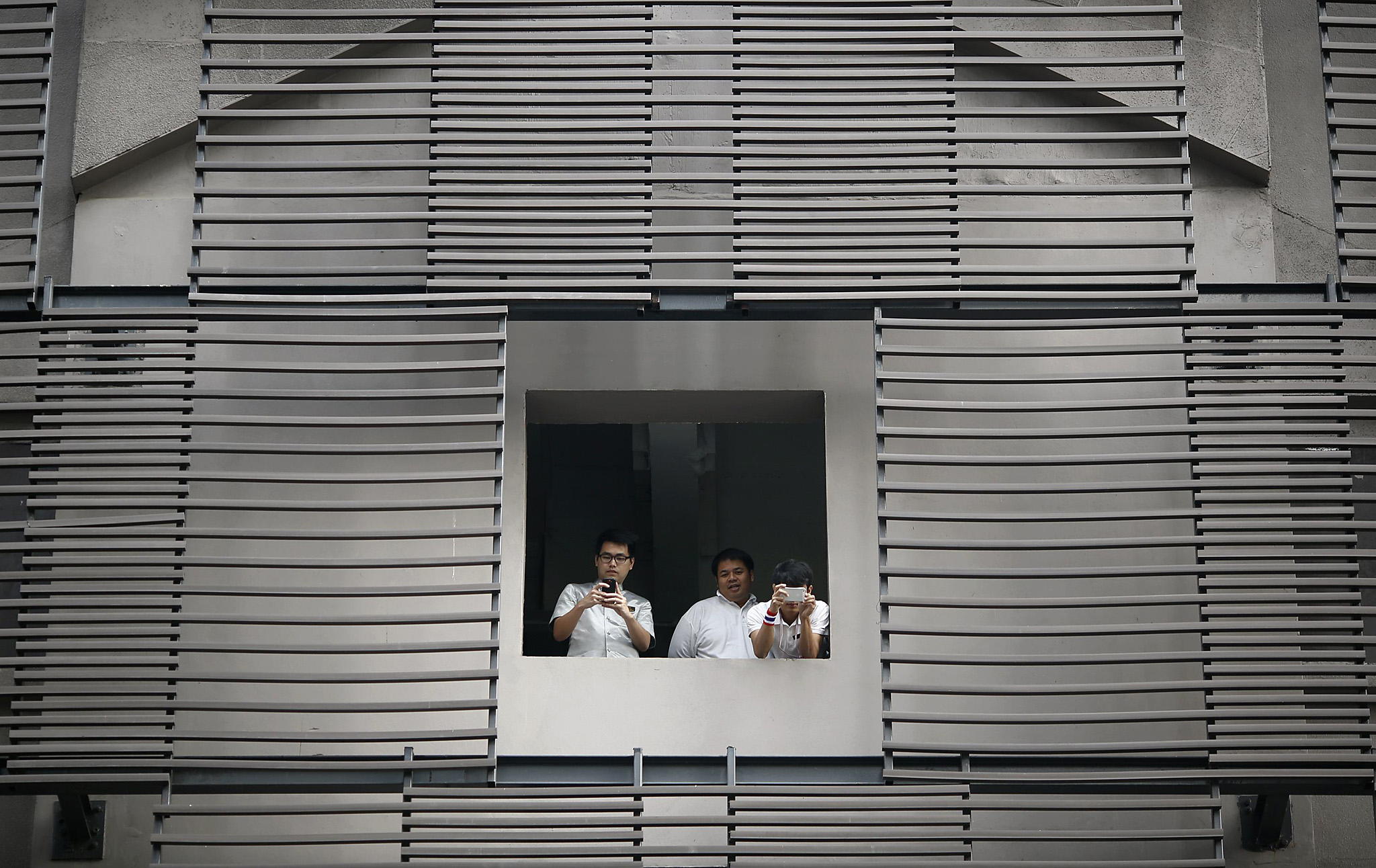 Employees take pictures though a window as anti-government protesters march through Bangkok's business district...Employees take pictures though a window as anti-government protesters march through Bangkok's business district January 23, 2014. The government declared a 60-day state of emergency from Wednesday hoping to prevent an escalation in protests now in a third month.  REUTERS/Damir Sagolj