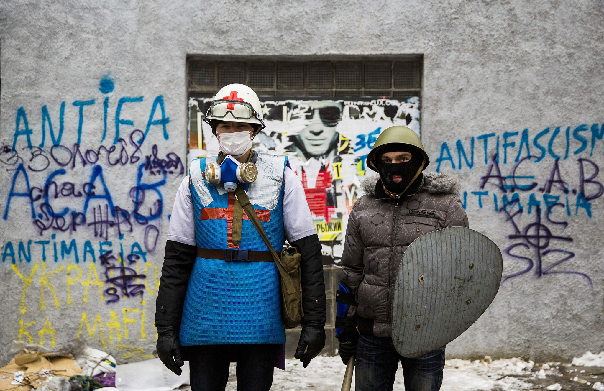 A medic of the anti-government protest camp poses for a portrait with his security guard at the barricades near the site of clashes with riot police in Kiev...A medic of the anti-government protest camp (L) poses for a portrait with his security guard at the barricades near the site of clashes with riot police in Kiev January 28, 2014. Ukrainian Prime Minister Mykola Azarov resigned on Tuesday while deputies loyal to President Viktor Yanukovich, acting to calm violent street protests, back-tracked and overturned anti-protest laws they rammed through parliament 12 days ago. REUTERS/Thomas Peter