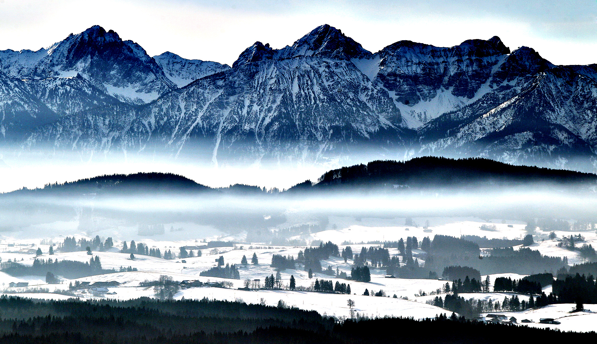 Fog covers the valleys in front of the Alpine panorama pictured from the Auerberg mountain near Stoetten, southern Germany.
