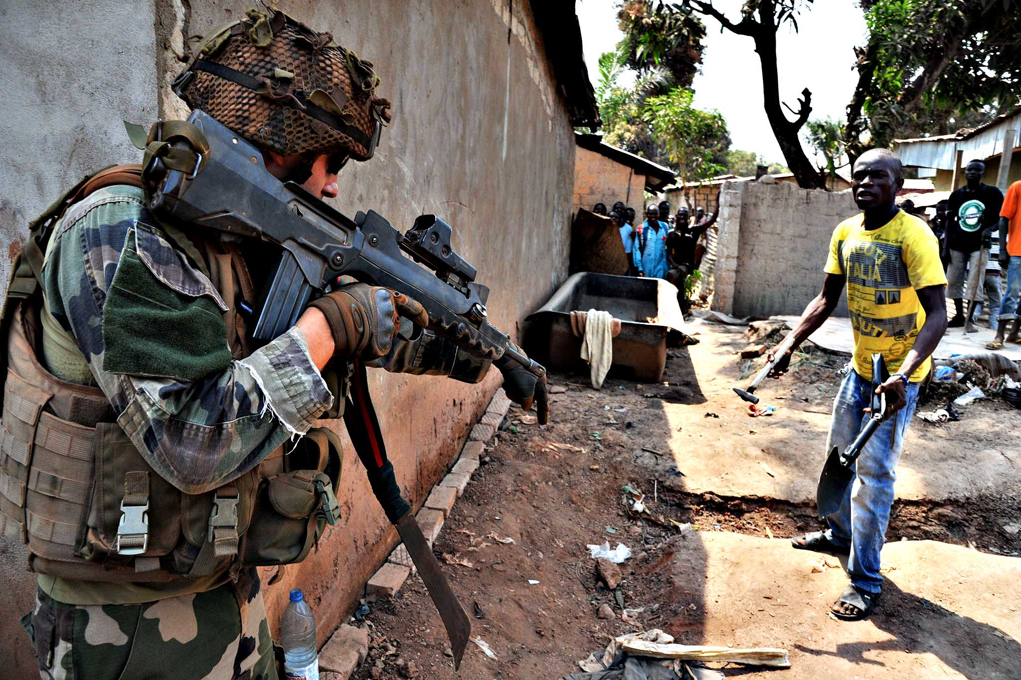 A French soldier of Operation Sangaris asks a man to put down his hammer and shovel during a patrol in Bangui on January 29, 2014. Gunfire erupted on January 29 in Bangui, still plagued by looting despite the security operations of French and African soldiers, now awaiting the reinforcement of a European force whose engagement has been authorized by the United Nations.