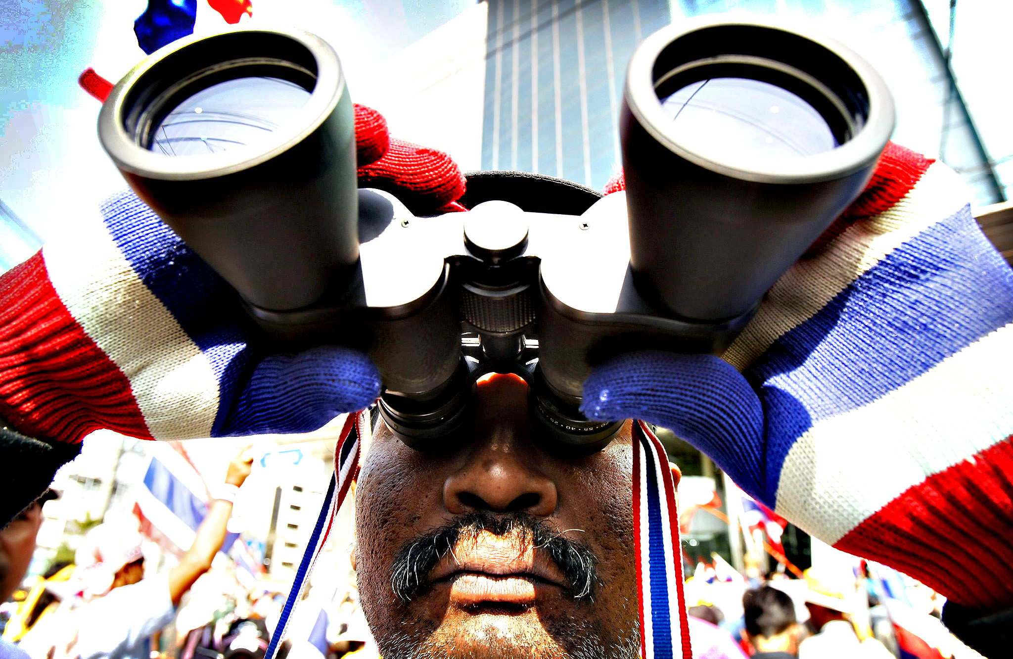 An anti-government protester uses a pair of binoculars during a rally in central Bangkok January 16, 2014. Protesters in Thailand trying to paralyse ministries to force the government to resign said they would target revenue offices on Thursday, but their numbers appeared to be dwindling and ministers say the movement could be running out of steam.