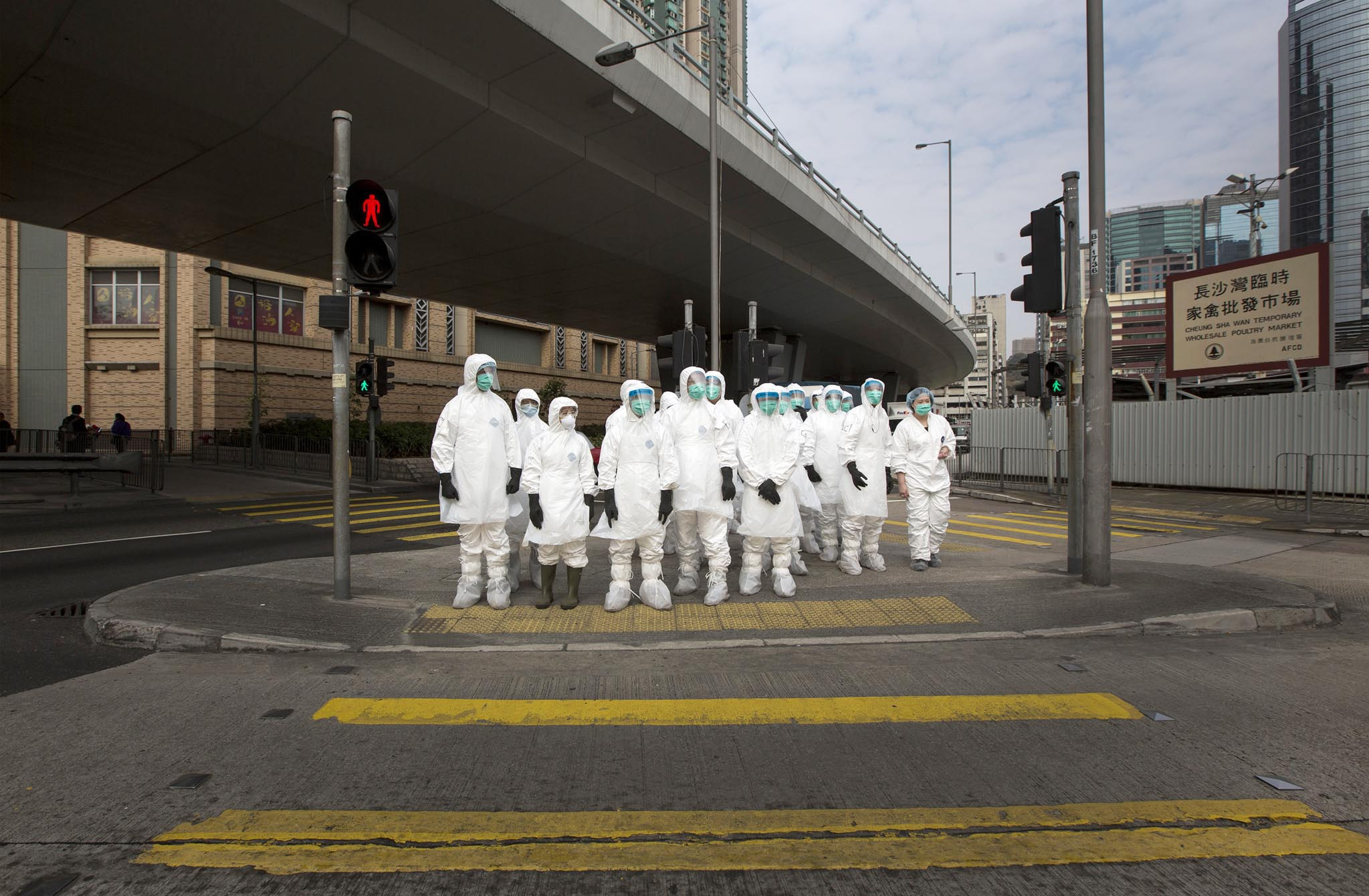 Health officers in full protective gear wait to cross a road near a wholesale poultry market in Hong Kong.