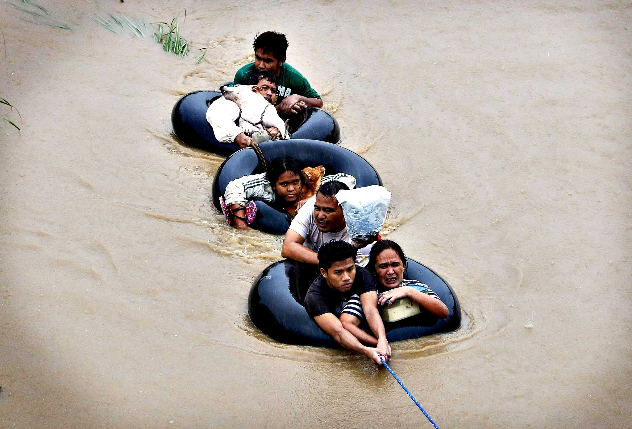 "Flood victims are pulled on inflatable tire tubes as they are evacuated from heavy flooding brought by tropical depression ""Agaton"", in Butuan, in the southern Philippine island of Mindanao January 20, 2014. Floods and landslides caused by tropical depression ""Agaton""  have killed 40 people and more than 500,000 people are displaced in Mindanao, the National Disaster Risk Reduction and Management Council reported on Sunday."