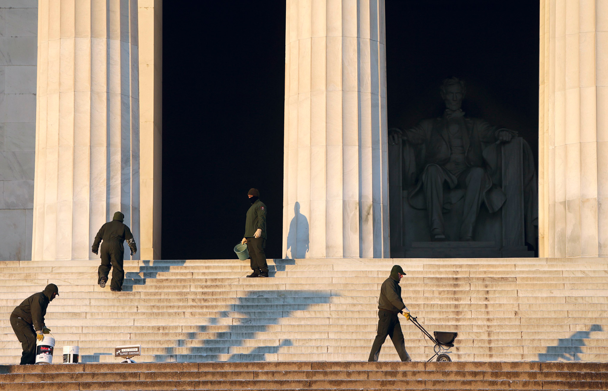 National Park Service workers spread salt on icy steps of the Lincoln Memorial in Washington...National Park Service workers spread salt on the icy steps of the Lincoln Memorial in Washington January 3, 2014. A heavy snowstorm and dangerously cold conditions gripped the northeastern United States on Friday, delaying flights, paralyzing road travel and closing schools and government offices across the region.  REUTERS/Gary Cameron