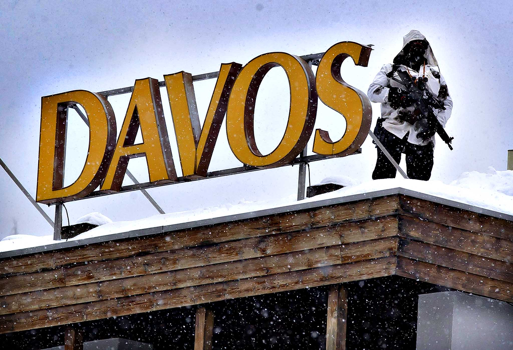 A member of Swiss special police forces stands on the roof of the Kongress Hotel next to the Congress Center in Davos, Switzerland, Tuesday, Jan. 21, 2014. The world's financial and political elite will head this week to the Swiss Alps for 2014  gathering of the World Economic Forum at the Swiss ski resort of Davos.