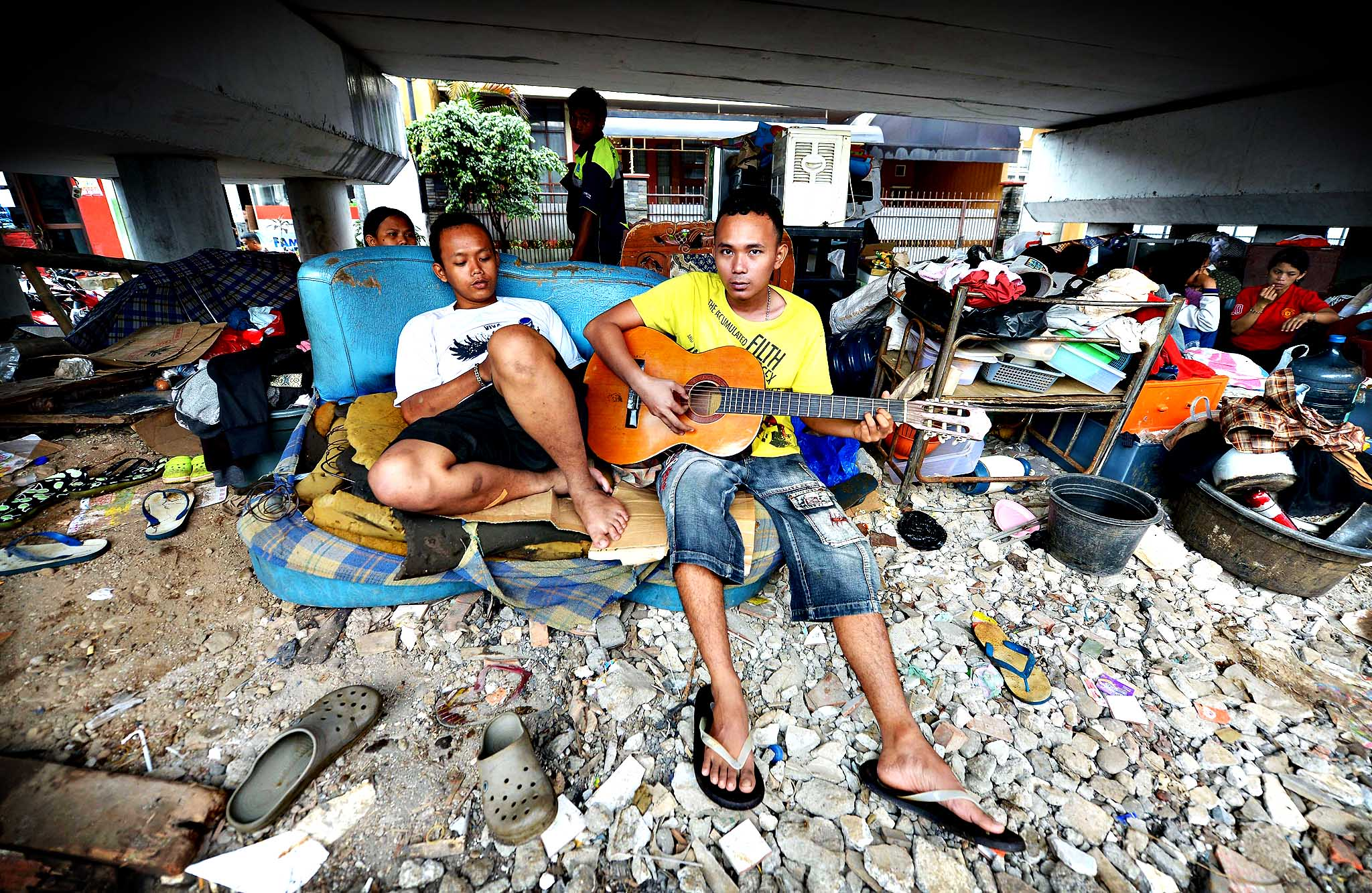 A man plays a guitar as flood affected people seek refuge under a bridge in Jakarta on January 21, 2014. More than 4,300 people in the capital have been displaced by the floods, which also worsened the city's notorious traffic jams.