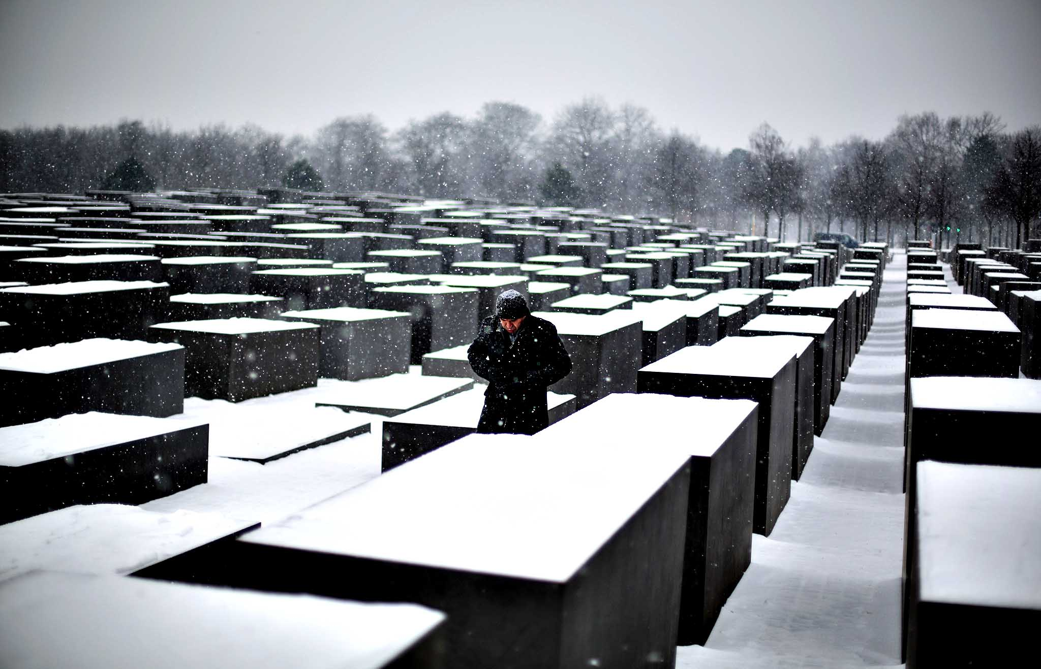 A man visits the snow covered Holocaust Memorial at the International Holocaust Remembrance Day in Berlin, Monday, Jan. 27, 2014. The German parliament Bundestag will hold a special remembrance session at the Reichstag building in commemoration of the liberation of the Auschwitz death camp on Jan. 27, 1045.
