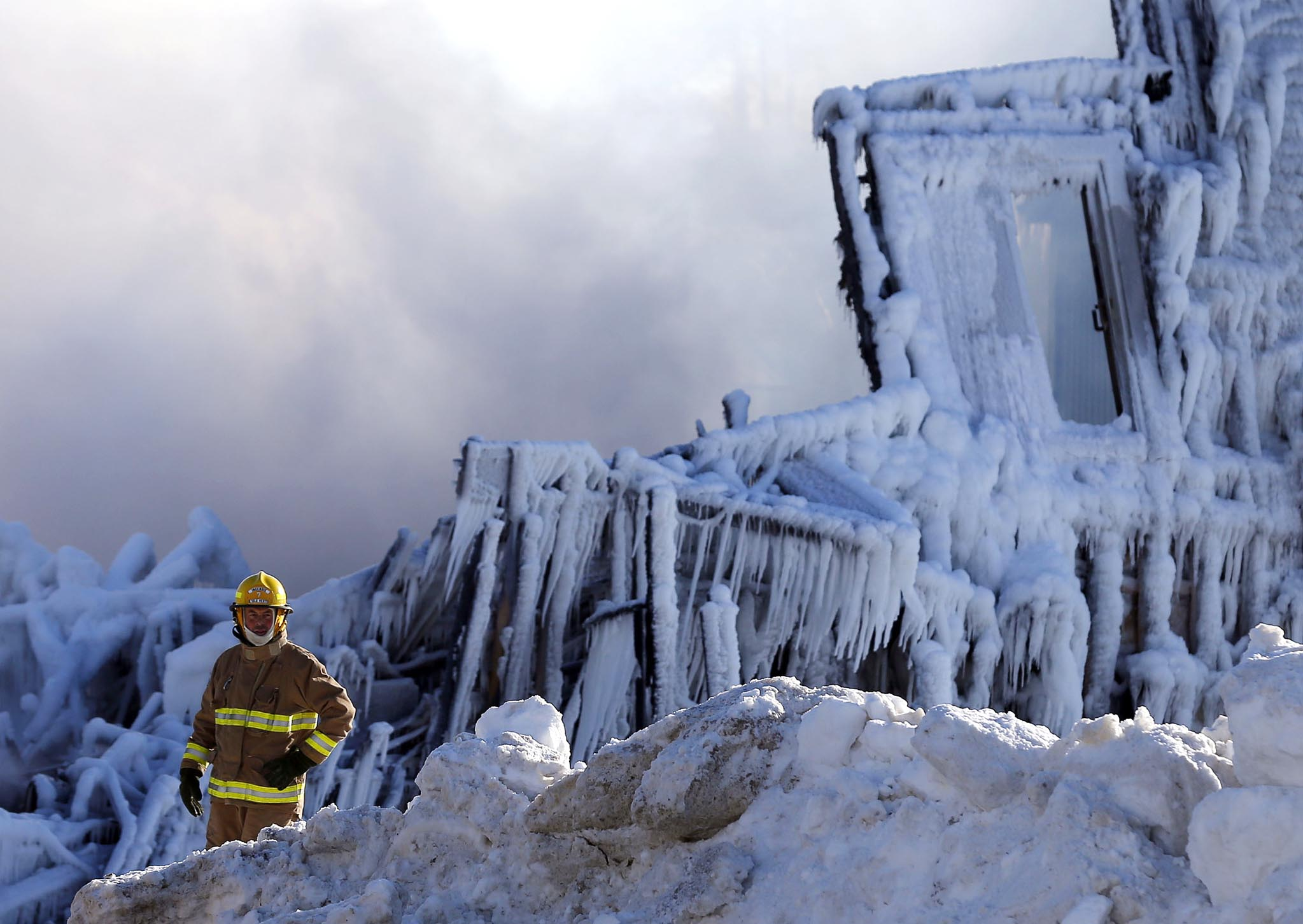 A firefighter looks on at the seniors residence Residence du Havre after a fire in L'Isle Verte, Quebec. REUTERS/Mathieu Belanger