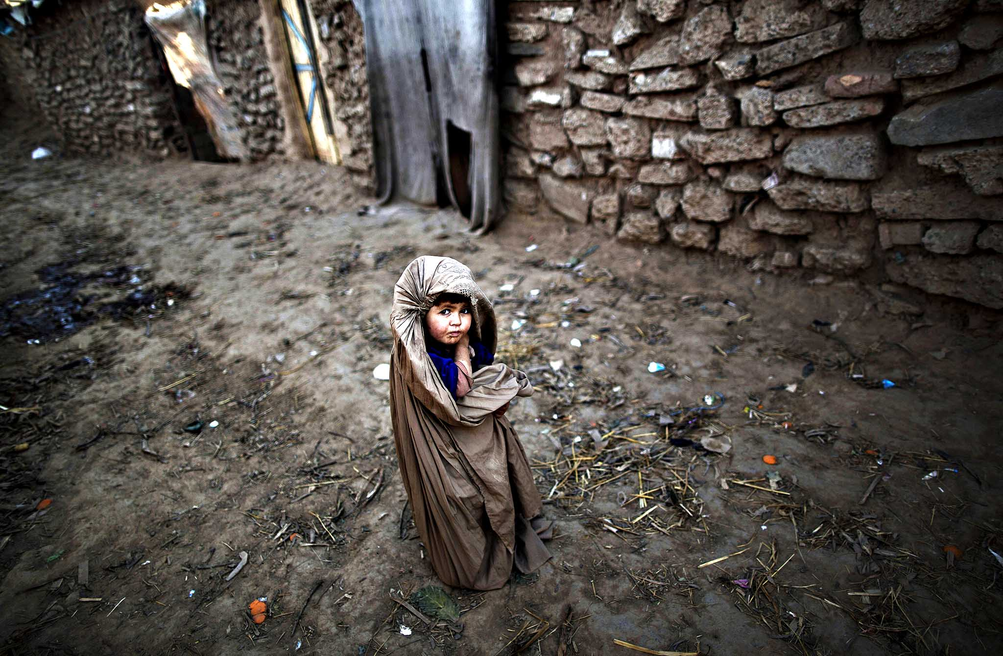 Dressed in a burqa, a Pakistani child, whose family was displaced from Pakistan's tribal areas due to fighting between the Taliban and the army, stands outside a mosque, where children heir daily Madrassa, or Islamic school, on the outskirts of Islamabad, Pakistan, Tuesday, Jan. 28, 2014.