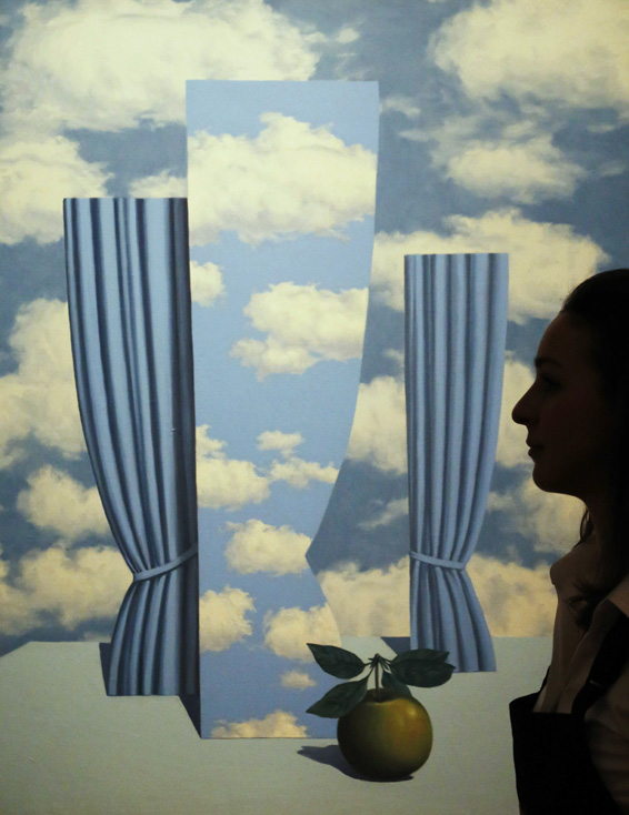 "An employee poses with artist Rene Magritte's artwork ""Le beau monde"" at Sotheby's auction house in London...An employee poses with artist Rene Magritte's artwork ""Le beau monde"" at Sotheby's auction house in London January 29, 2014.  The work is estimated to sell for 6 million GB pounds (9 million U.S. dollars) when auctioned in February at Sotheby's in London. REUTERS/Luke MacGregor"