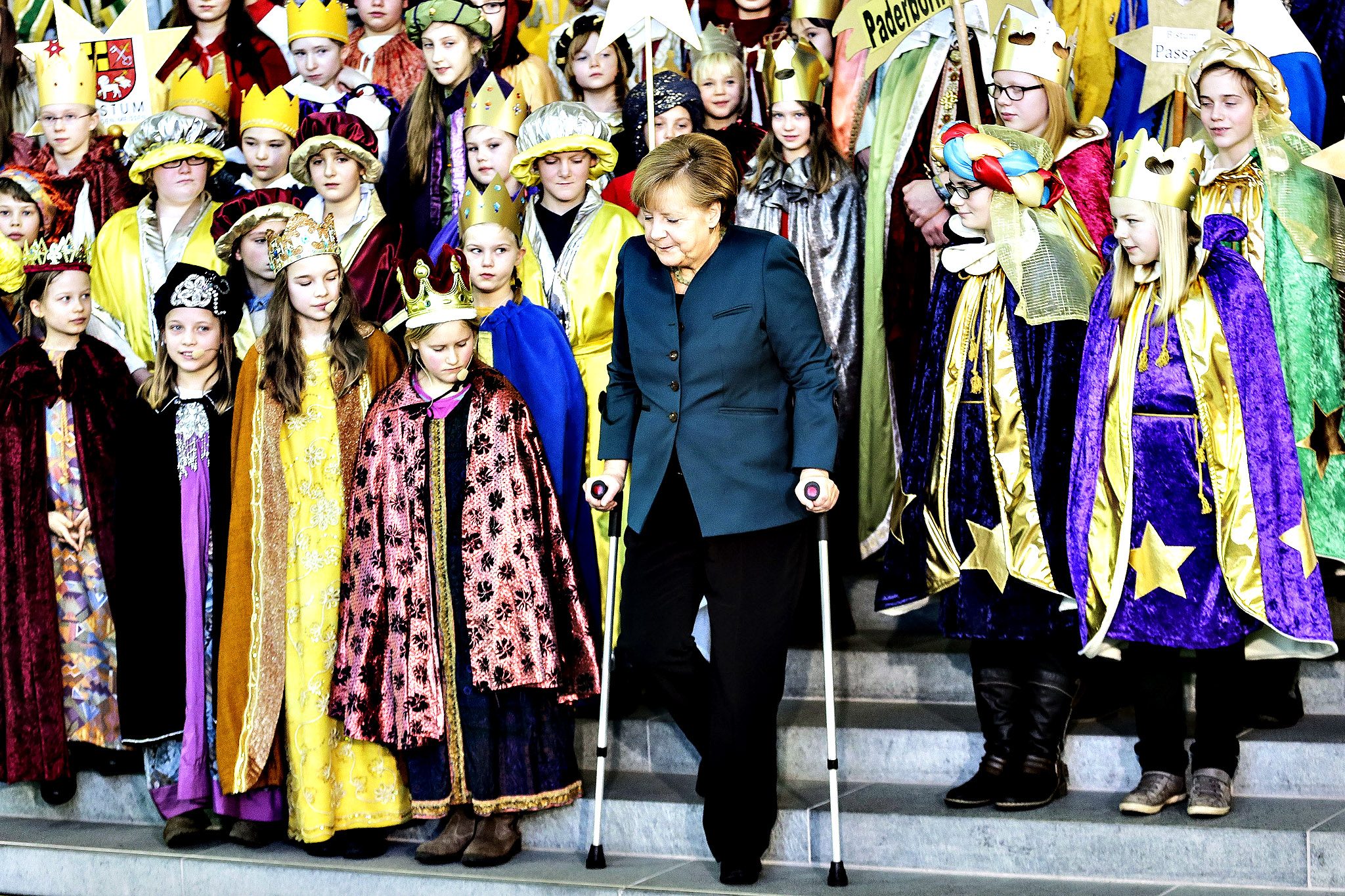 German Chancellor Angela Merkel  uses  crutches as she attends the annual reception for Carolers at the chancellery in Berlin,  Tuesday Jan. 7, 2014. German Chancellor Angela Merkel  suffered a  pelvis  injury during ski holidays  in the Swiss Alps and will have to cut back on her work schedule for the next three weeks.