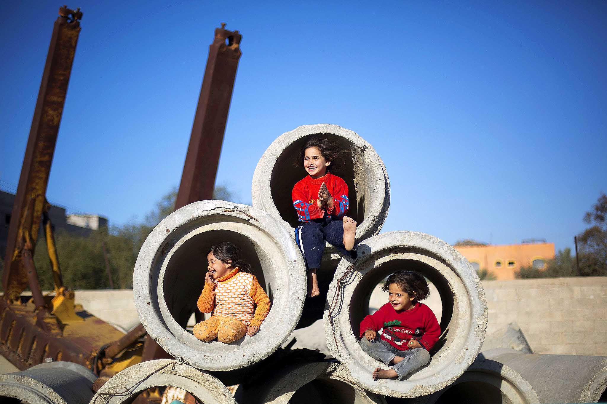 Palestinian children play with concrete pipes in Gaza City, on January 28, 2014.
