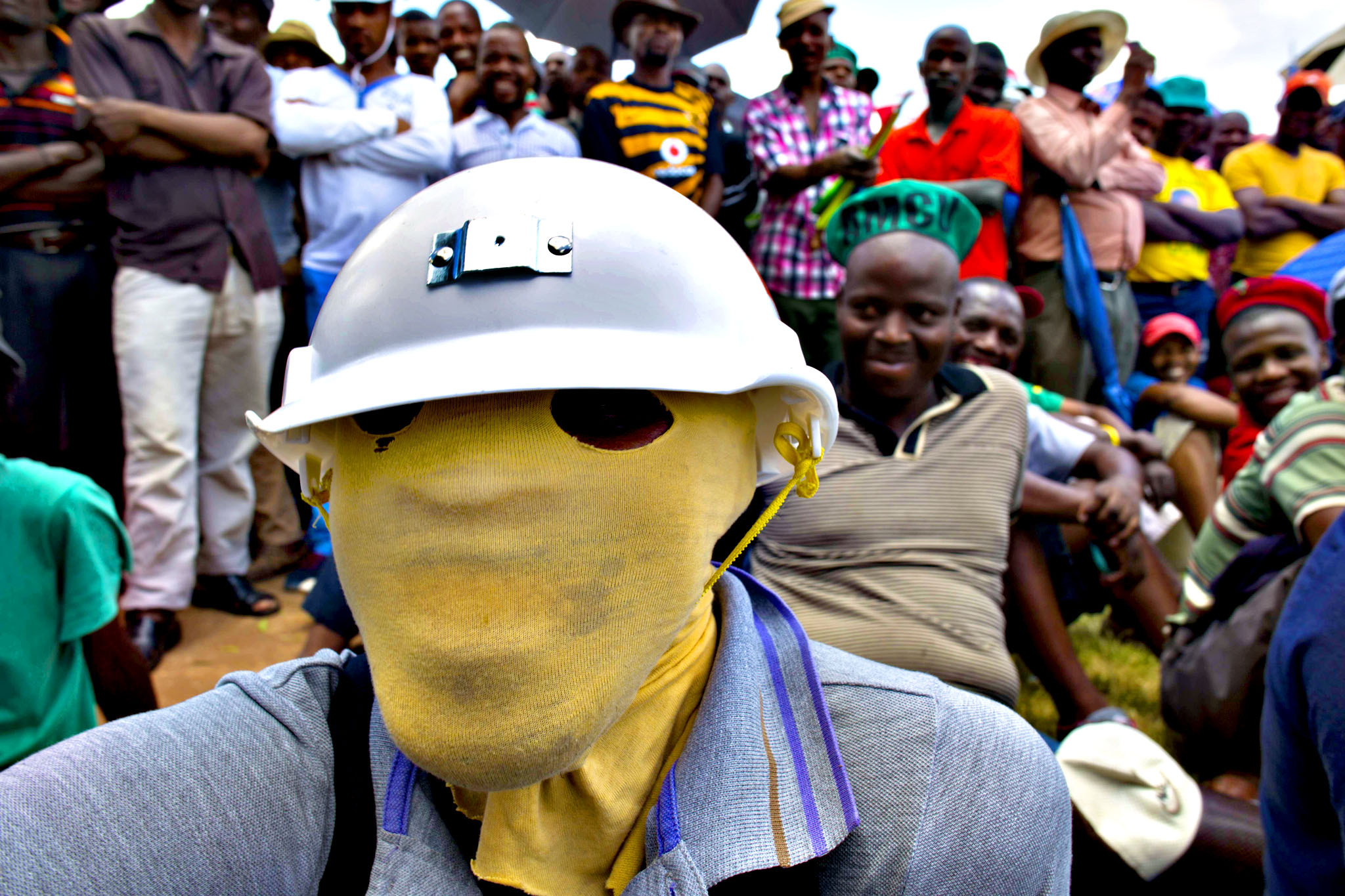 A man carrying a helmet and with his face hooded attends a rally near Lonmin's platinum mine in Marikana on January 23, 2014. Tens of thousands of workers at the world's three top platinum producers were set to down tools today in a pay strike that could have a devastating impact in Africa's largest economy. Up to 80,000 workers at Impala Platinum, Anglo American Platinum and Lonmin mines will embark on an indefinite strike from early Thursday, after their demand to double the minimum monthly wage to $1,150 was rejected.