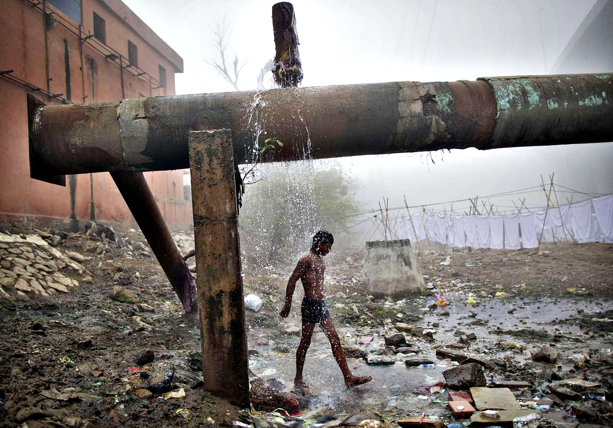 A man bathes under a broken water pipeline at a riverside on a cold winter morning in New Delhi January 20, 2014.