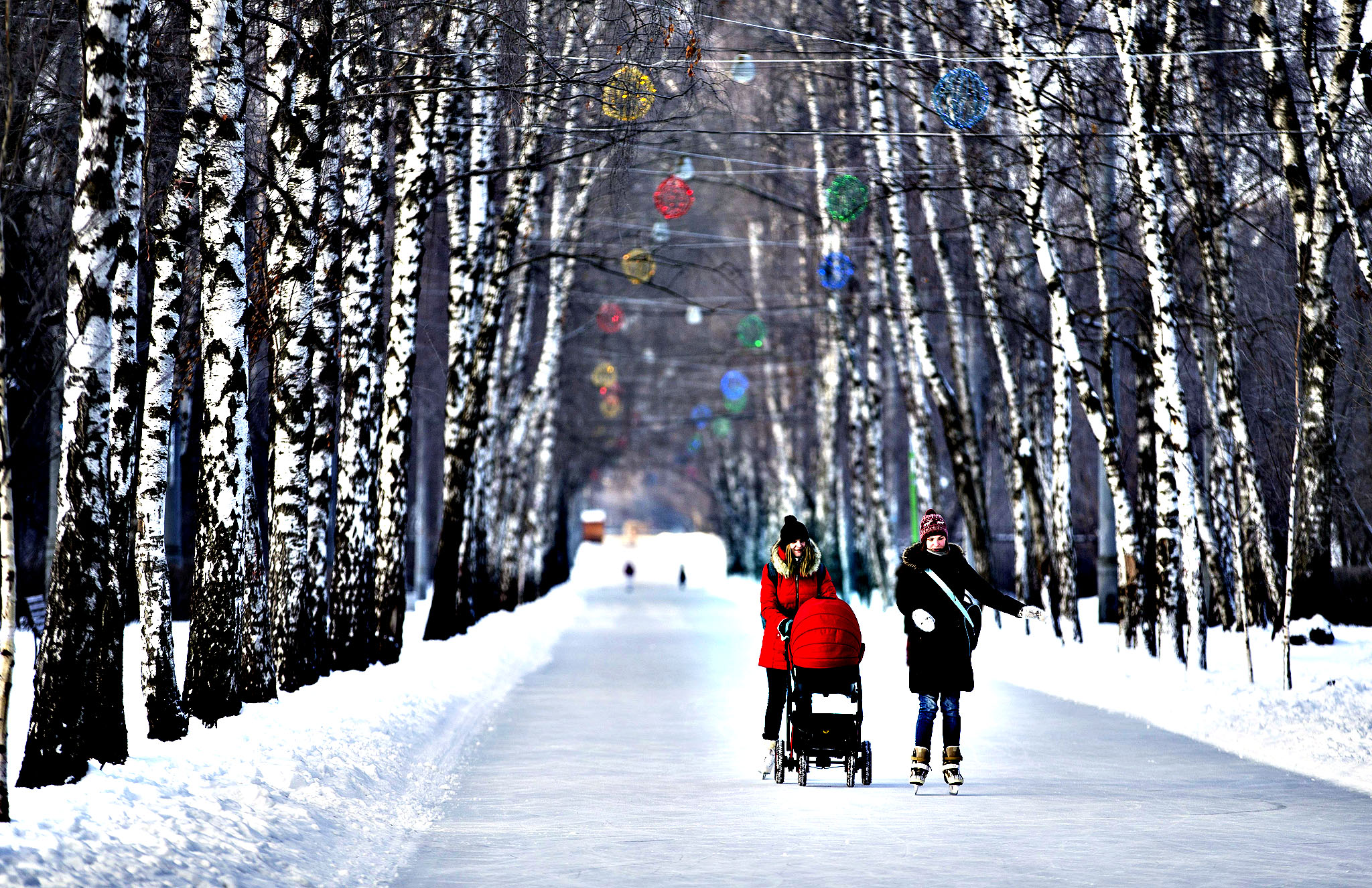 Russian women enjoy a skating rink along a boulevard, one of them with a baby carriage in Moscow's Sokolniki Park, Russia, Thursday, Jan. 23, 2014.  The temperature in Moscow is minus 15 Celsius (5 Fahrenheit).