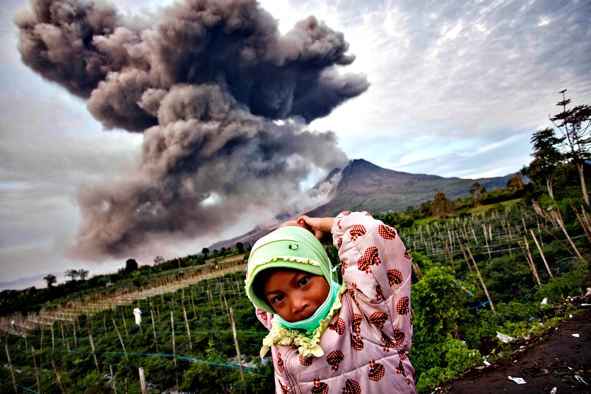 A girl stands in the foreground as Mount Sinabung spews pyroclastic smoke on January 8, 2014 in Karo District, North Sumatra, Indonesia. The number of displaced people has increased to 22,000 in Western Indonesia as Mount Sinabung continues to spew ash and smoke after several eruptions since September. Eleven deaths have now been recorded as a result of the eruptions with hundreds more falling ill. Officials expect the number of evacuees to rise as volcanic activity remains high.