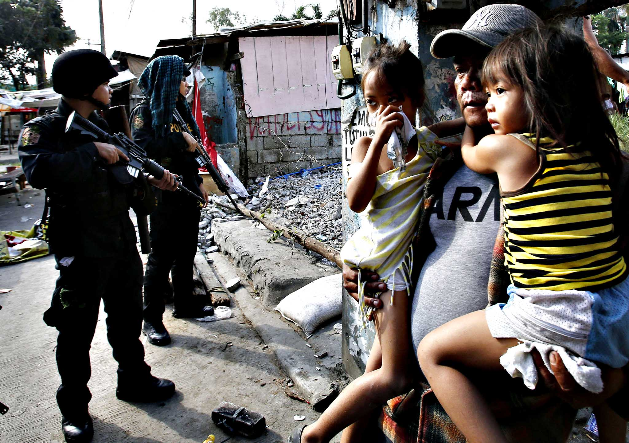 A squatter dweller carries his children as they leave their shanty house during the demolition of a squatter colony in Quezon city, Metro Manila. Dozens were hurt during clashes triggered by the demolition of a squatter settlement for business developments in suburban Quezon city on Monday, local media reported.