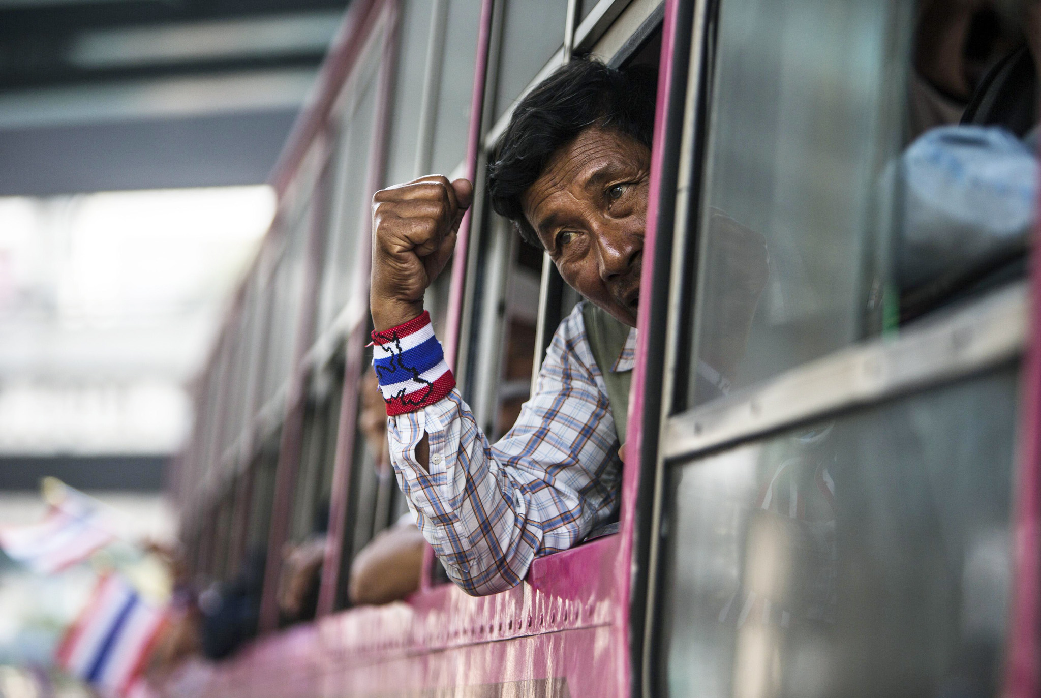 An anti-government protester gestures out of a bus window as he travels to an office for the Land Transportation Department in Nonthaburi province, on the outskirts of Bangkok...An anti-government protester gestures out of a bus window as he travels to an office for the Land Transportation Department in Nonthaburi province, on the outskirts of Bangkok, January 29, 2014. Hundreds of anti-government protesters travelled to the provincial office on Wednesday and demanded employees leave the building and suspend operations.  REUTERS/Nir Elias (THAILAND - Tags: CIVIL UNREST POLITICS TRANSPORT)