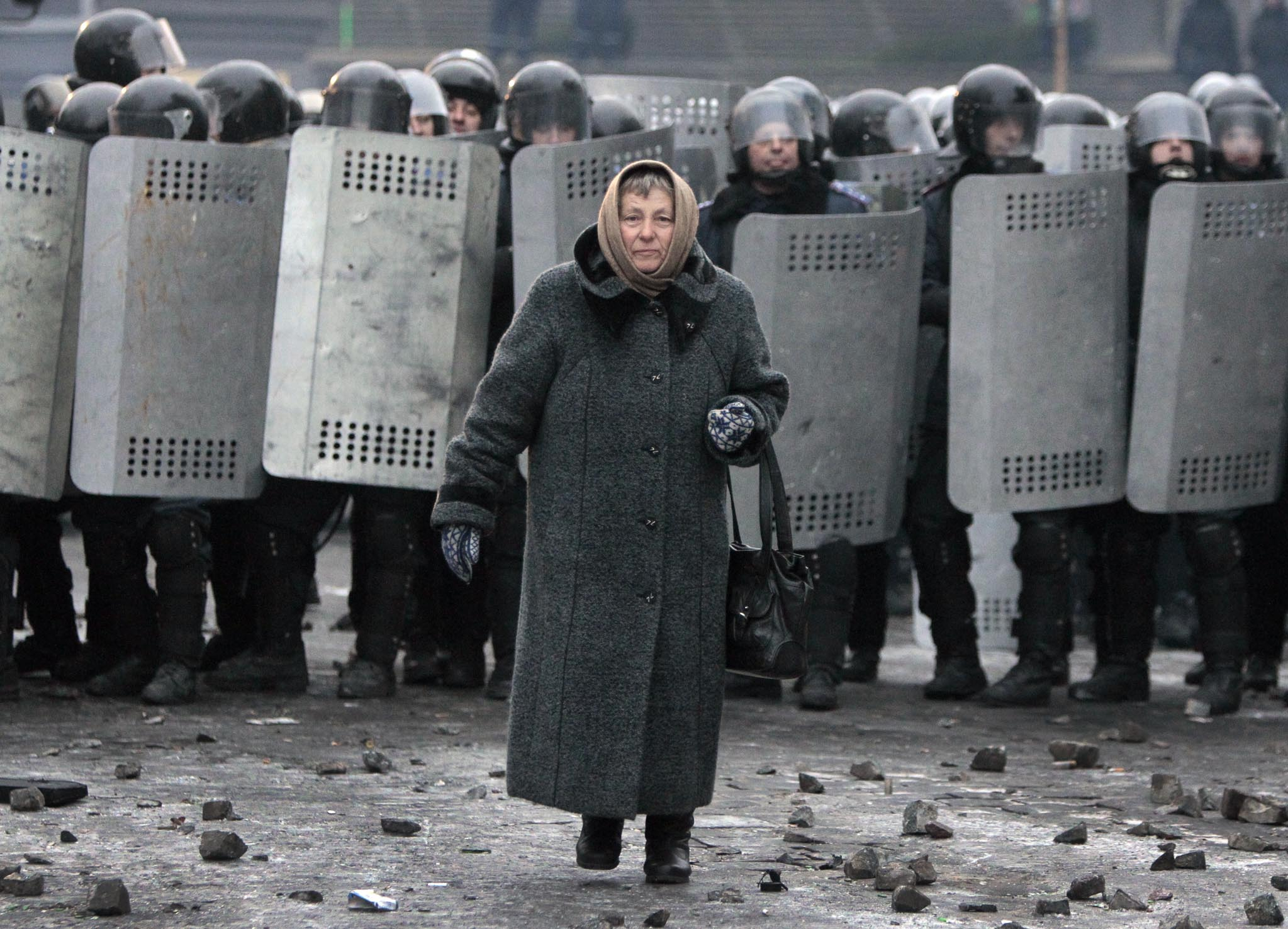 An elderly woman walks from police officers as they block a street during unrest in central Kiev, Ukraine,Tuesday, Jan. 21, 2014. Anti-government protesters