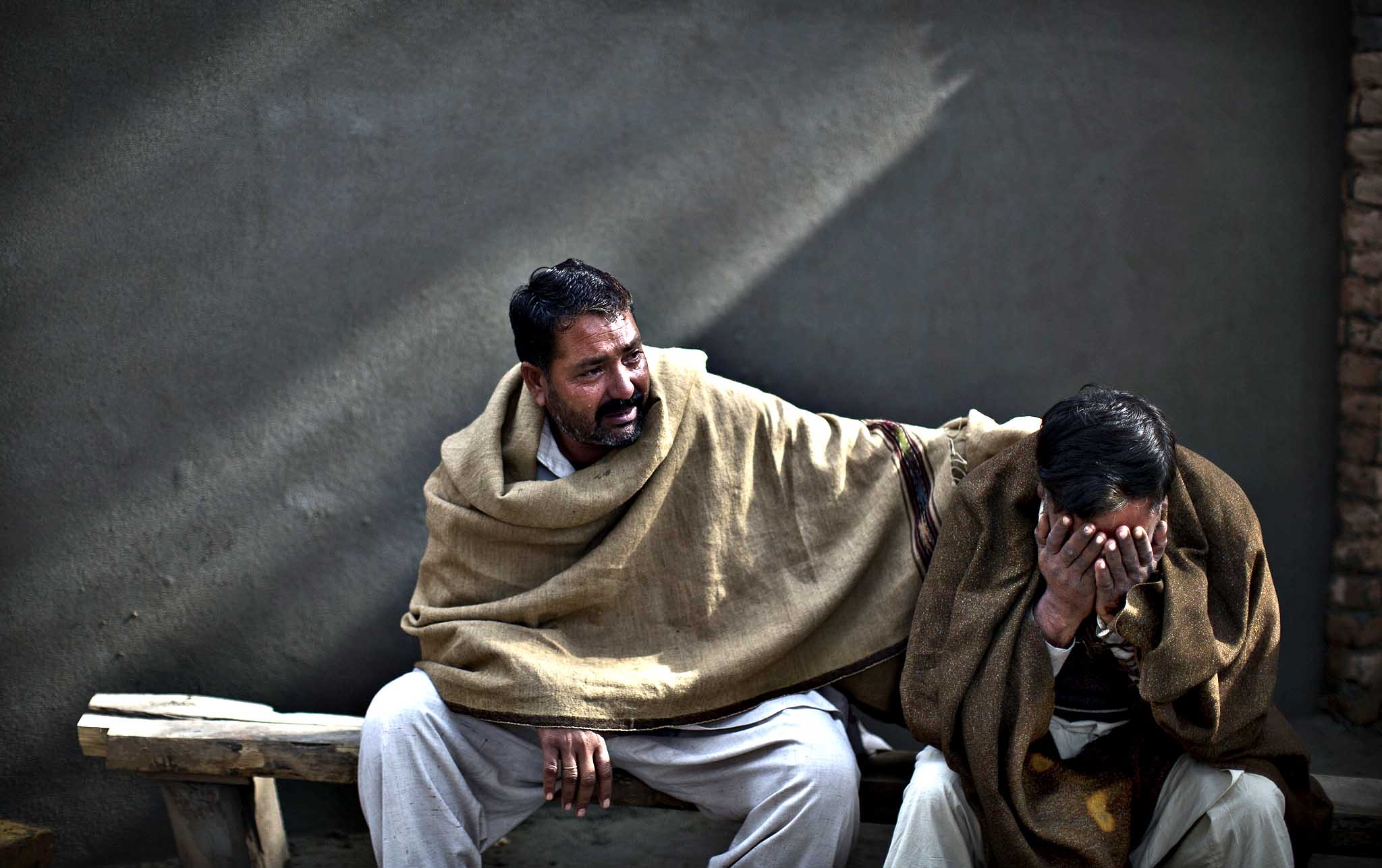 Uncles of Pakistani student, Zoubair Latif, 17, who was killed in a suicide bombing, mourn his death while waiting at a hospital to take the body for burial, in Rawalpindi, Pakistan, Monday, Jan. 20, 2014. A Taliban suicide bomber blew himself up not far from Pakistan s military headquarters Monday, killing more than a dozen of people a day after a militants bombing inside an army compound in the northwest of the country, officials and militants said.