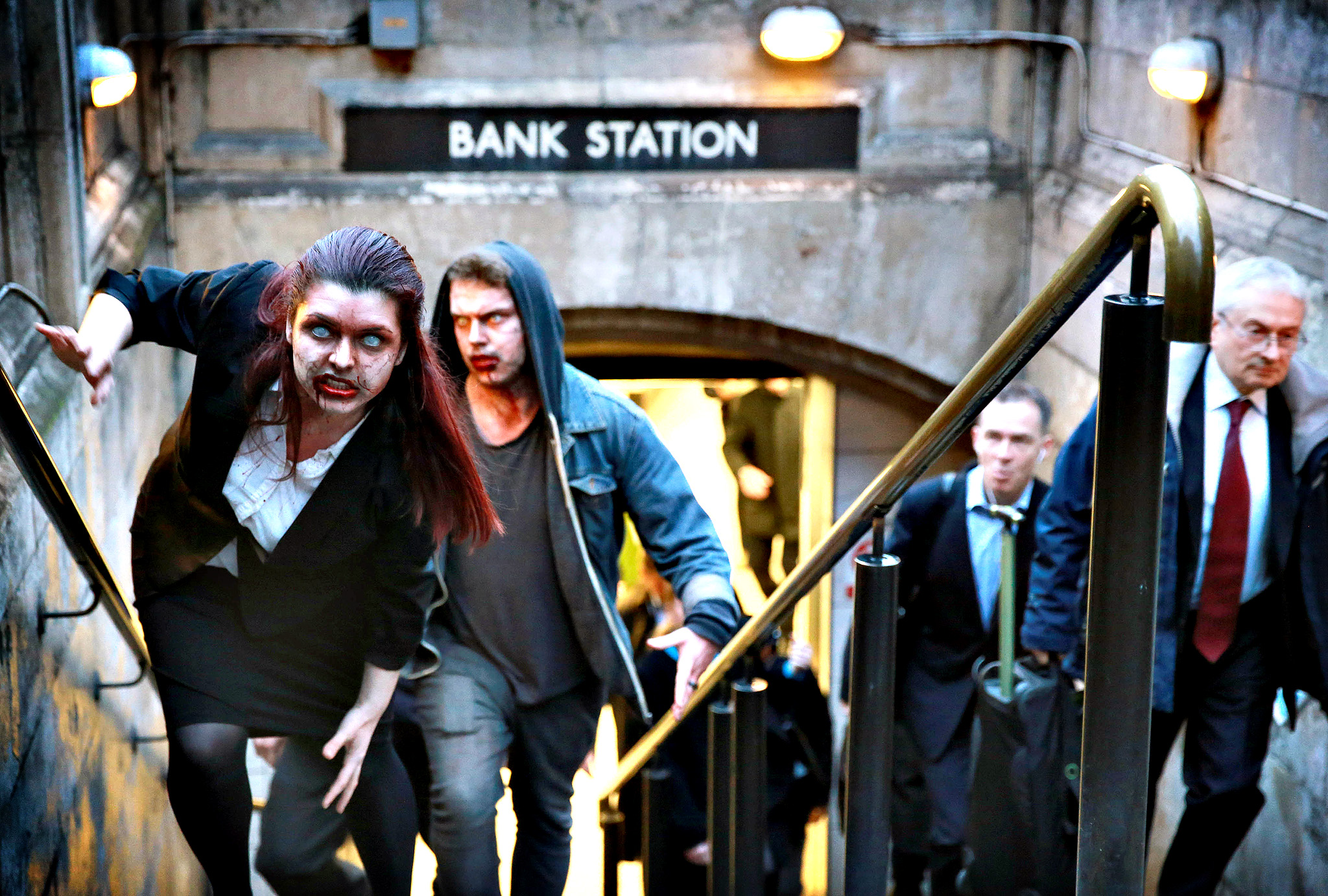 Actors dressed as zombies exit Bank Station in London as peer-to-peer lender RateSetter highlights the issue of 'zombie' savings accounts with  lifeless returns . PRESS ASSOCIATION Photo. Picture date: Wednesday January 15, 2014. The independent study commissioned by RateSetter found that 79% of Britons do not check their savings returns against inflation, with some falling as low as 0.1% earning just  1 a year on savings of  1,000.