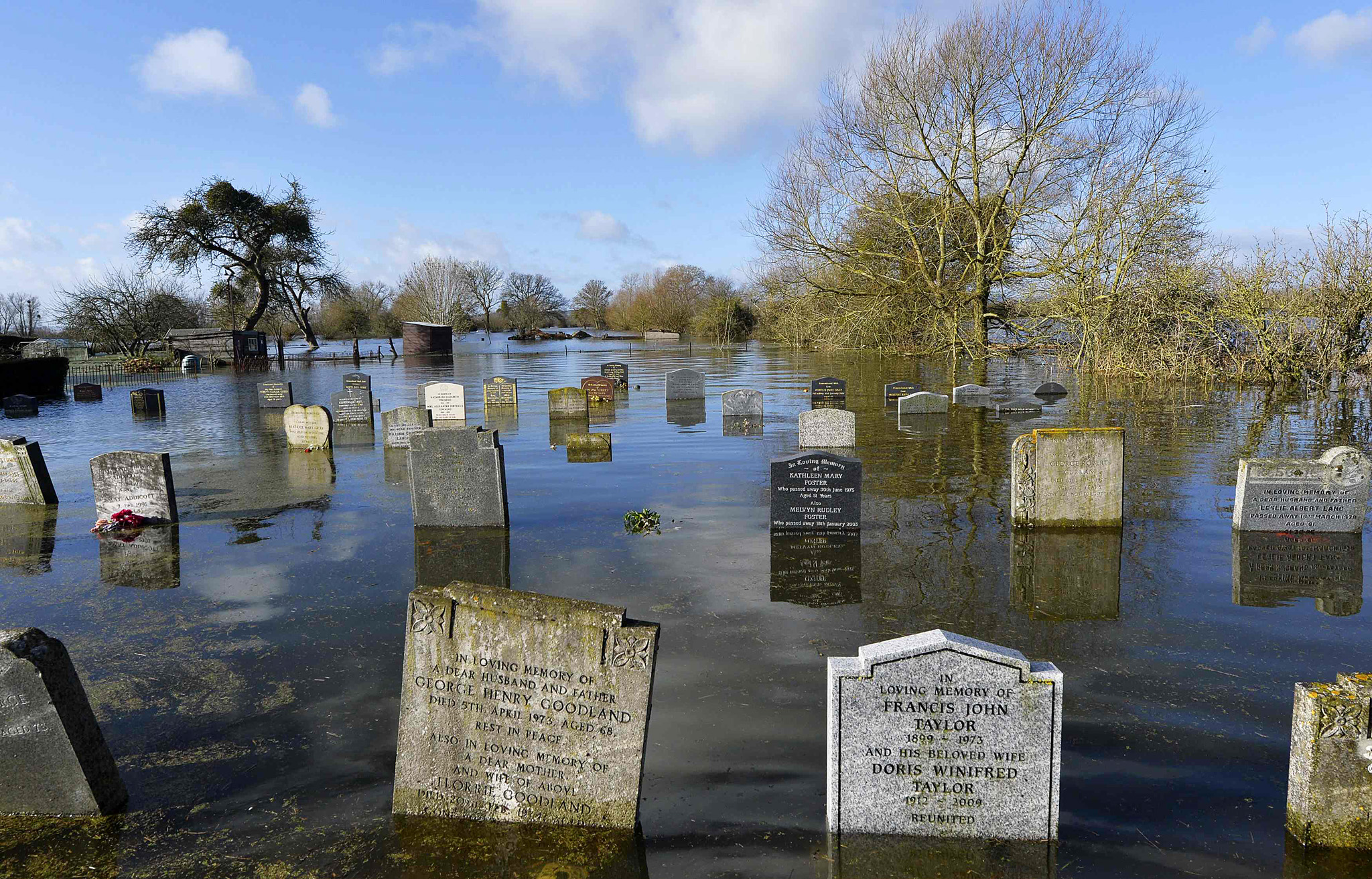 A graveyard is seen underwater in the village of Moorland in south west England...A graveyard is seen underwater in the village of Moorland in south west England February 7, 2014. Many areas of the Somerset Levels have been underwater for over a month in the wettest January in Britain on record. Severe weather warnings for rain and gale force winds have been issued for the weekend. REUTERS/Toby Melville (BRITAIN - Tags: SOCIETY ENVIRONMENT TPX IMAGES OF THE DAY)