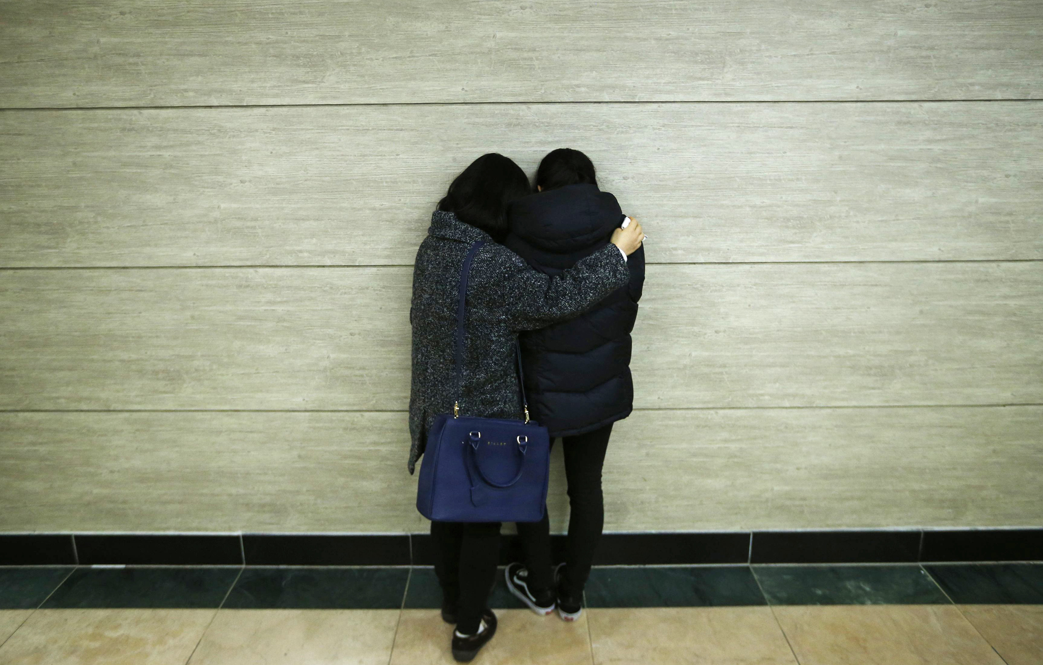 Relatives of victims who were killed when a resort building collapsed, comfort each other at a group memorial altar in Gyeongju...Relatives of victims who were killed when a resort building collapsed, comfort each other at a group memorial altar in Gyeongju, about 375 km (235 miles) southeast of Seou February 18, 2014.  Ten people attending a welcoming party for new university students were killed when a building at a South Korean mountain resort collapsed late on Monday, emergency officials said, trapping dozens in snow and rubble for several hours. About 560 students had gathered in the auditorium of the golf resort in the mountains in the city of Gyeongju, around 375 km (235 miles) southeast of Seoul. Heavy snow had built up on the roof of the prefabricated building, causing it to collapse, fire department officials said.   REUTERS/Kim Hong-Ji
