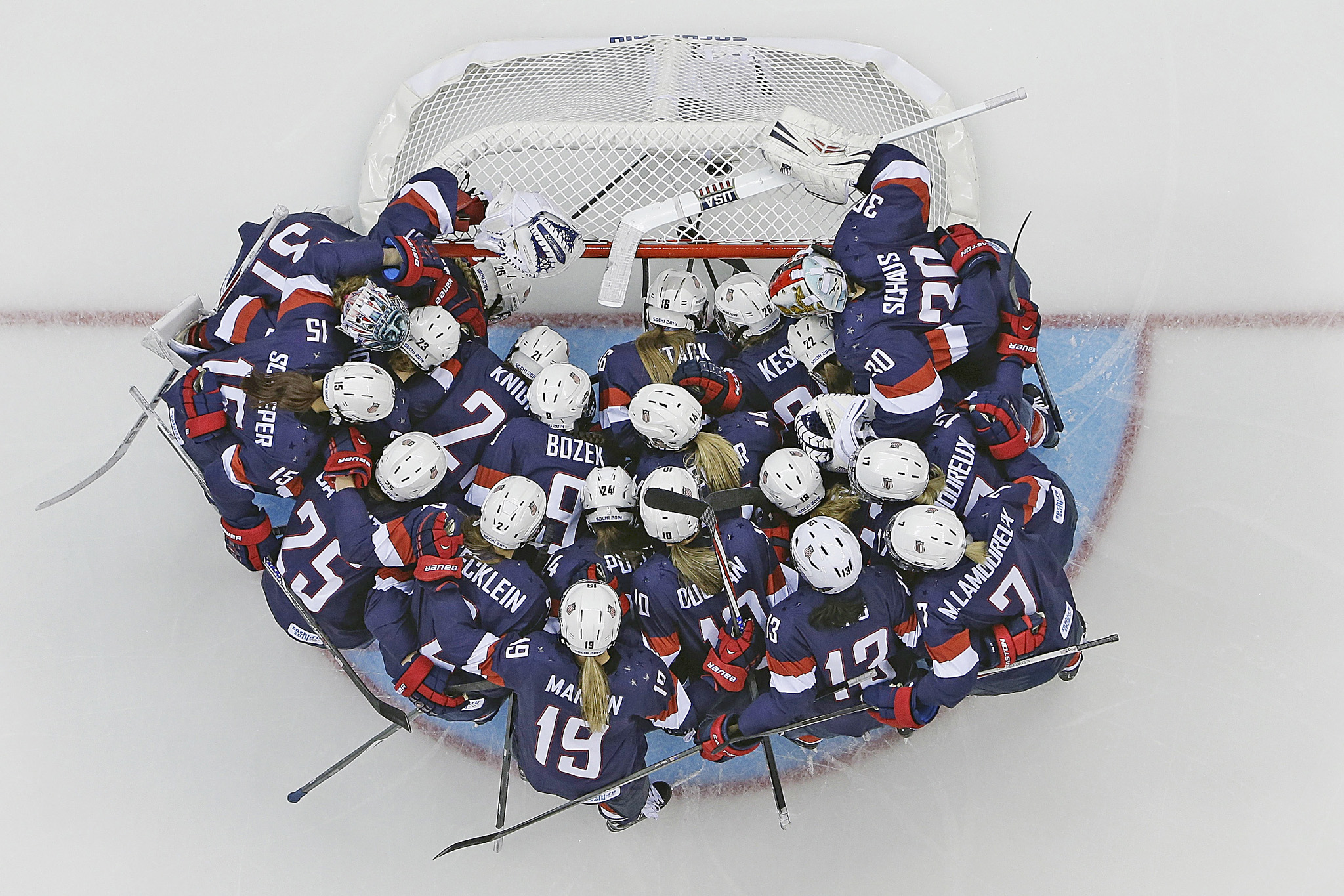 Team USA huddles around the net before the game against Switzerland during the 2014 Winter Olympics women's ice hockey game at Shayba Arena, Monday, Feb. 10, 2014, in Sochi, Russia. (AP Photo/Matt Slocum )